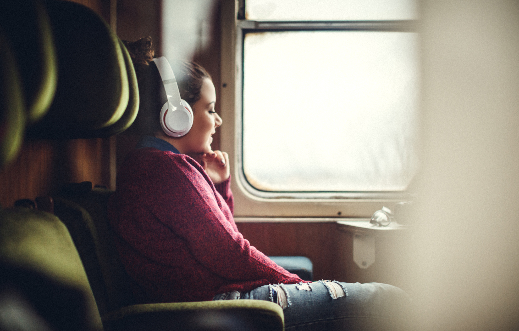 Smiling woman listening to music on smart phone in subway