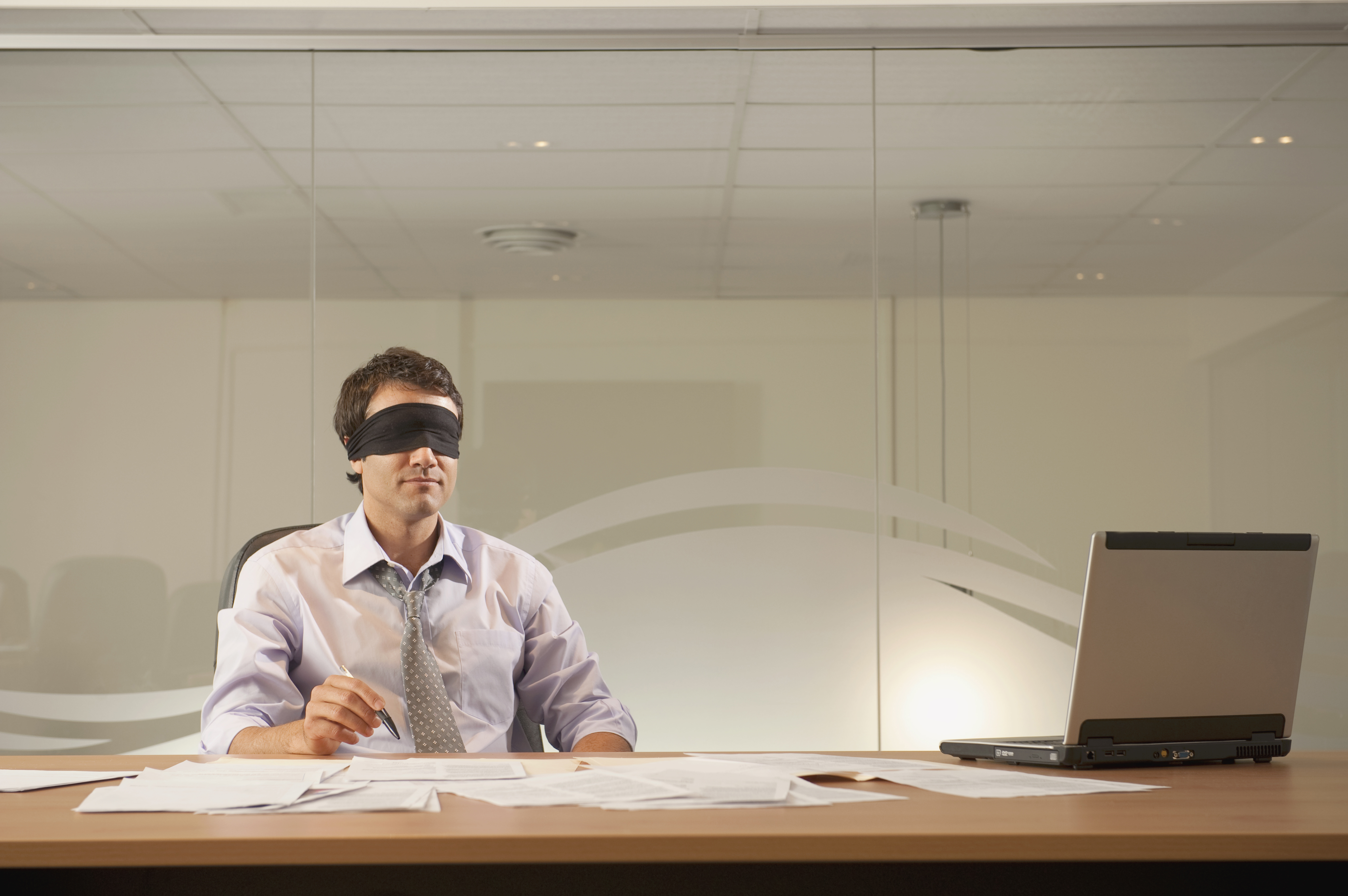 Businessman wearing a blindfold at his desk