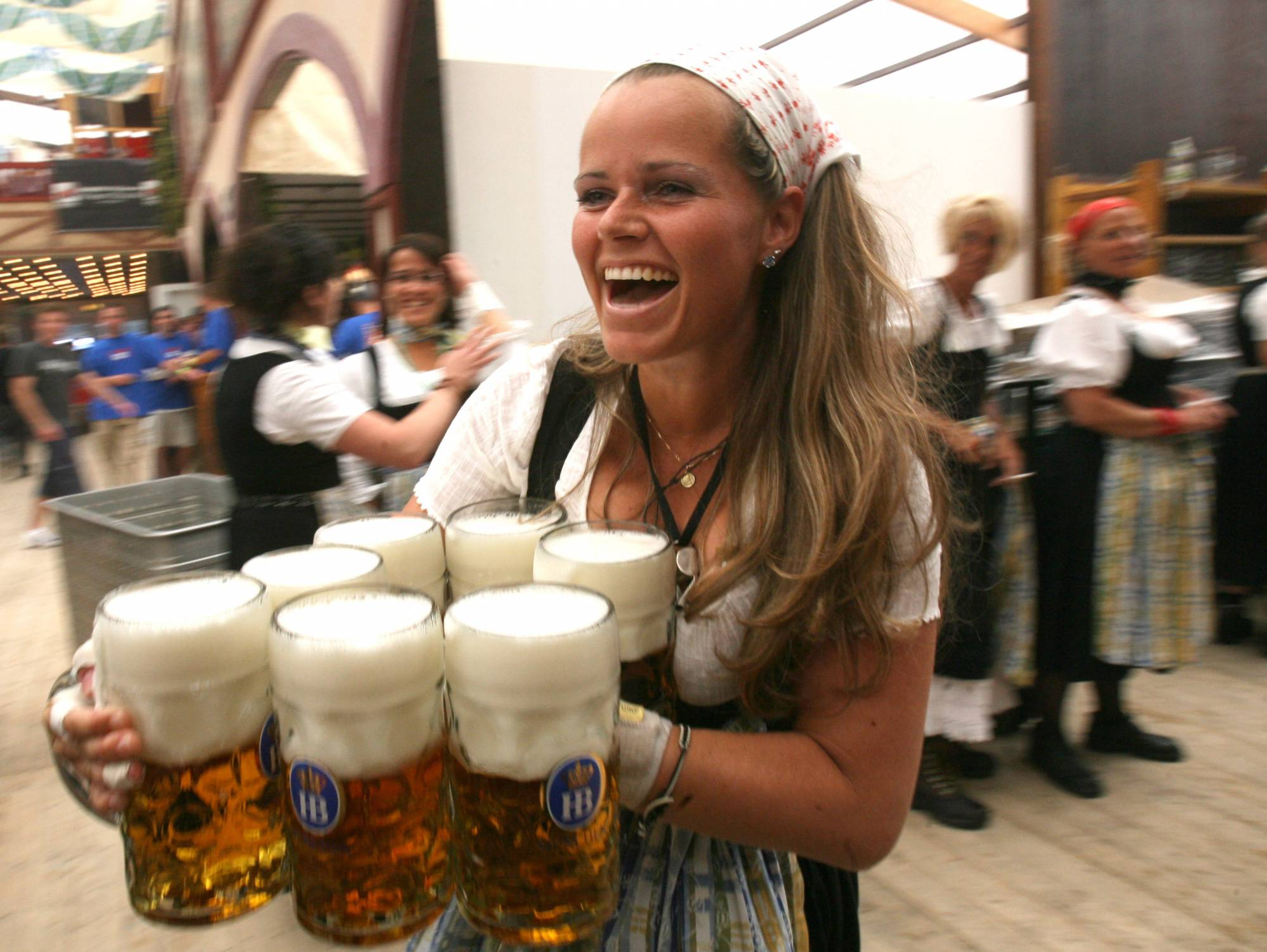 Bavarian waitress carries beer after the opening of the Octoberfest in Munich