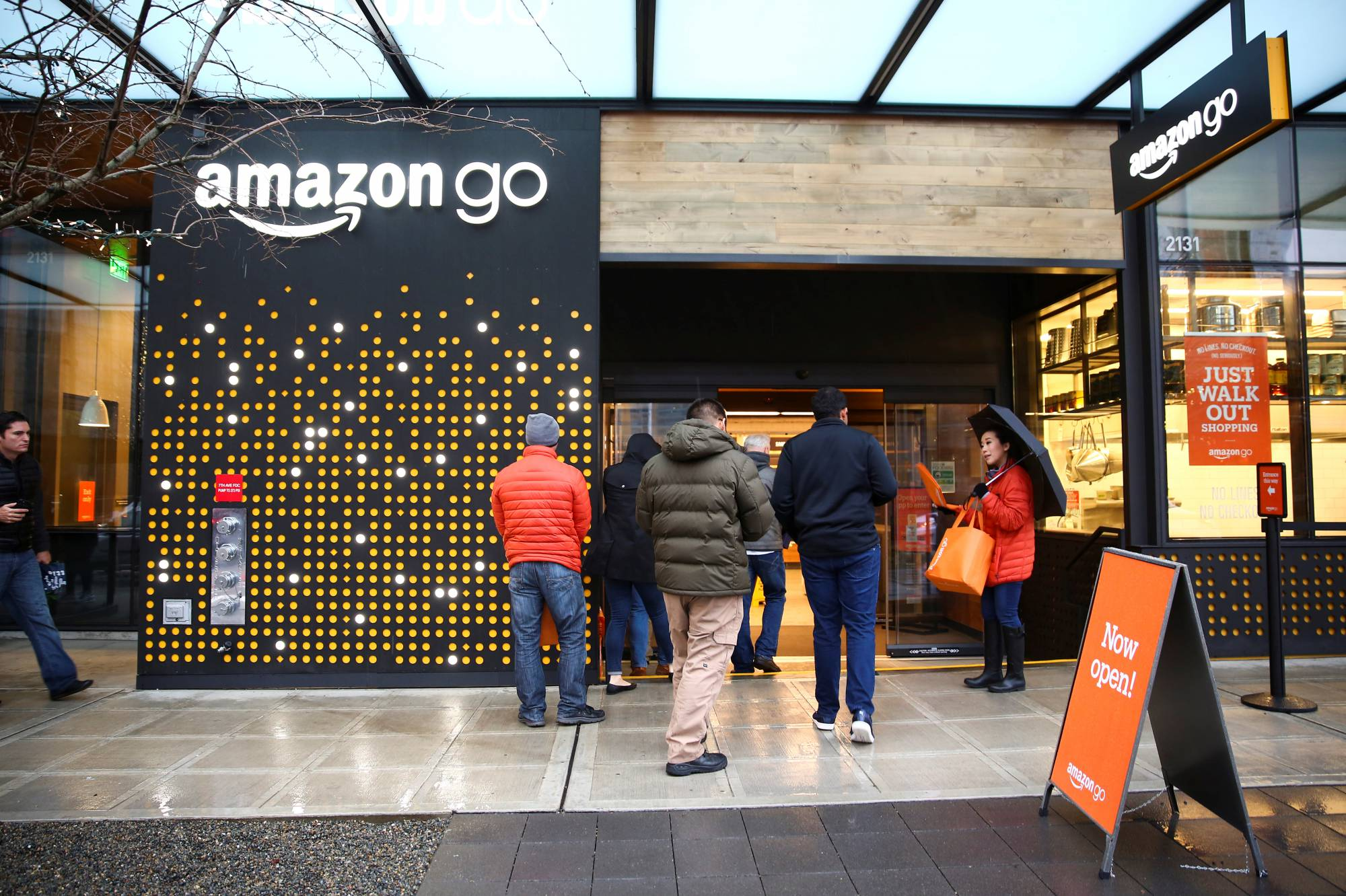 People are offered free reusable bags as they enter the new Amazon Go store in Seattle