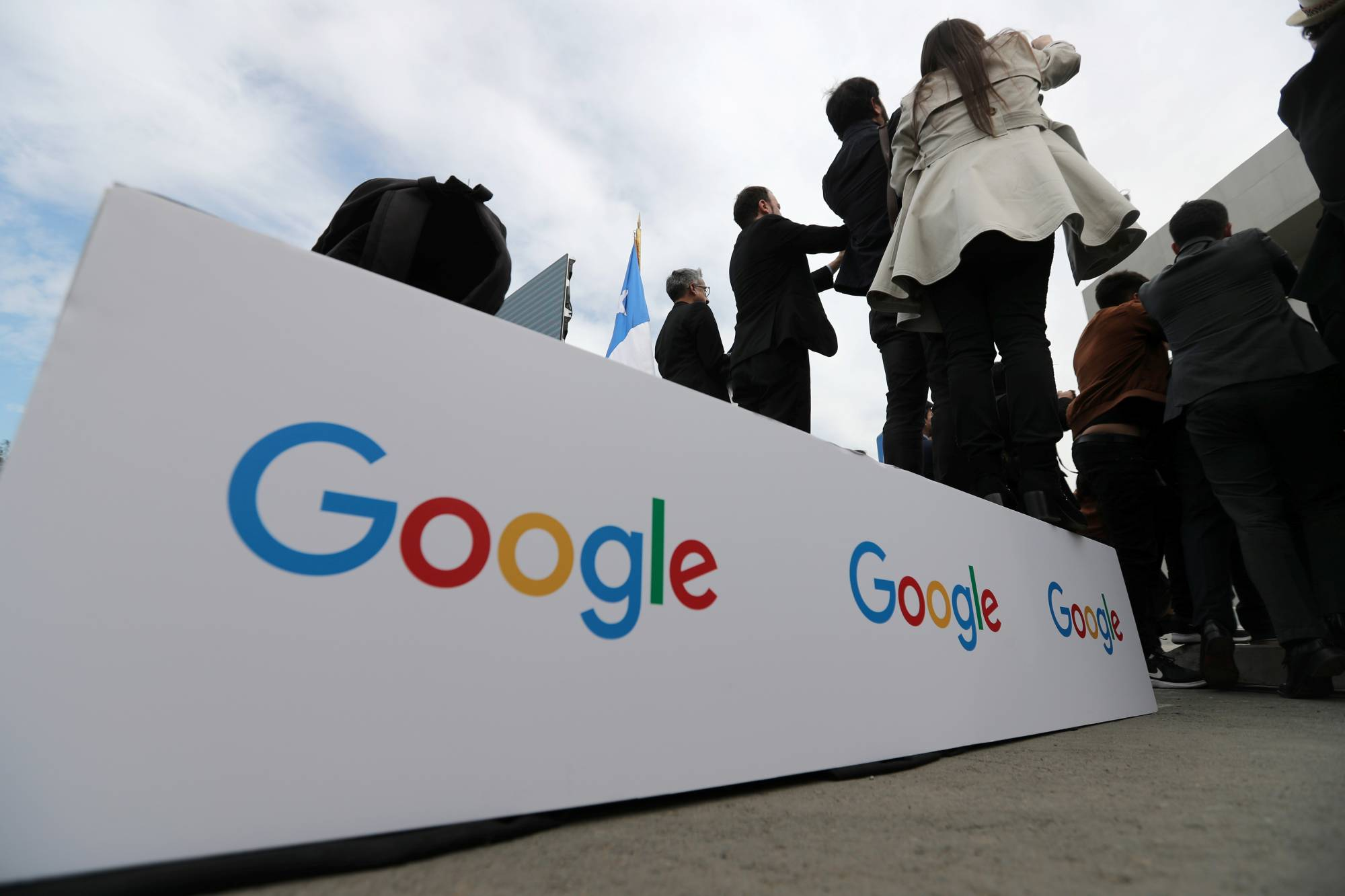 Guests stand on a podium with the Google logo during the announcement of the plans for their data centre expansion in Santiago