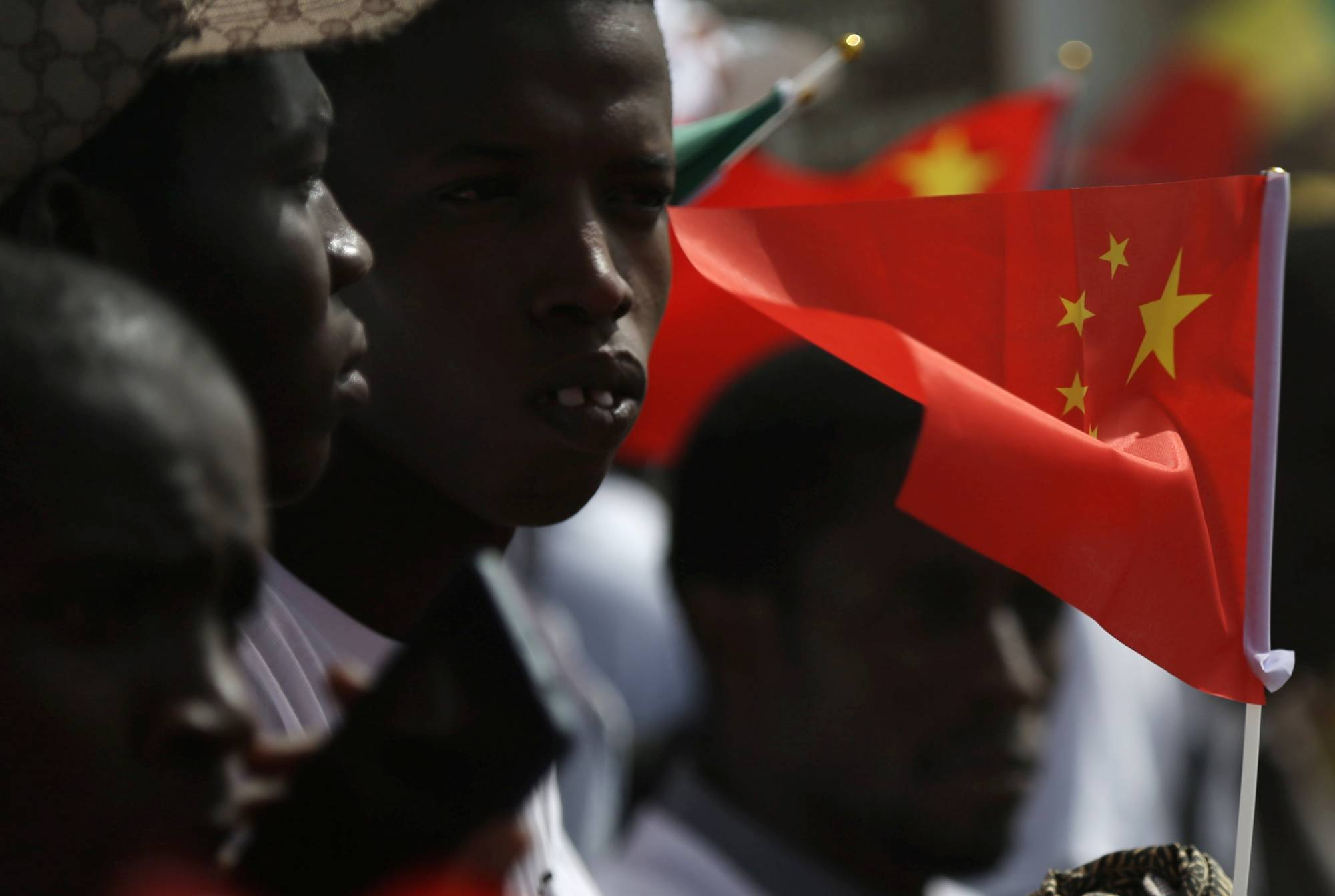 Well wishers holding flags wait for the arrival of Chinese President Xi Jinping at the Leopold Sedar Senghor International Airport at the start of his visit to Dakar