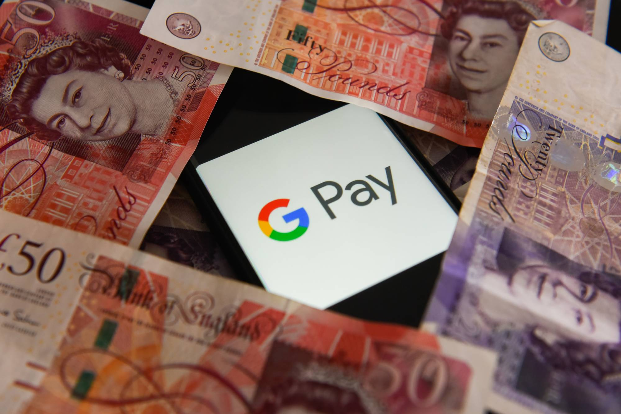 Fifty and twenty pounds bank notes and Google Pay logo are