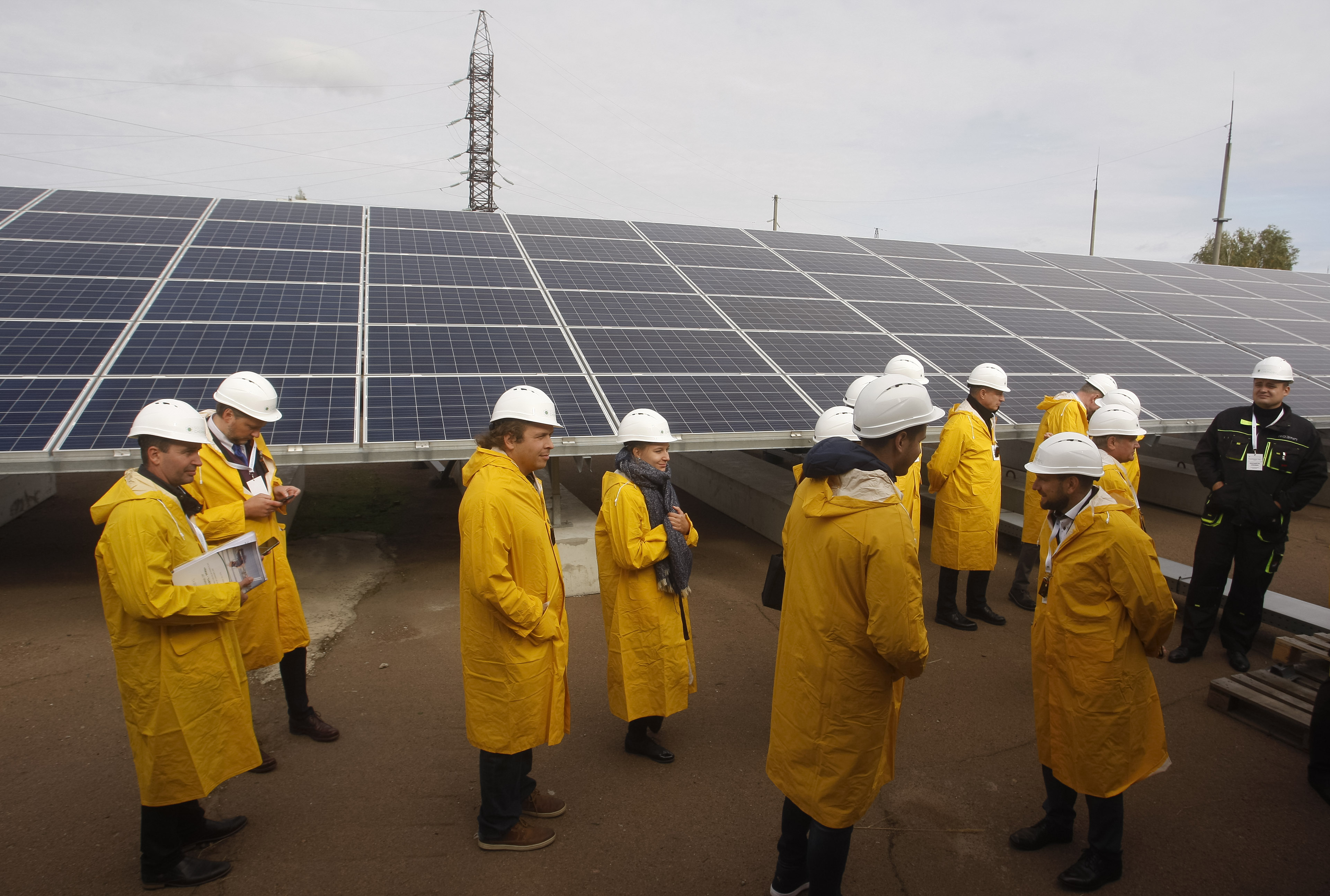 Visitors seen standing next to a solar photovoltaic elements