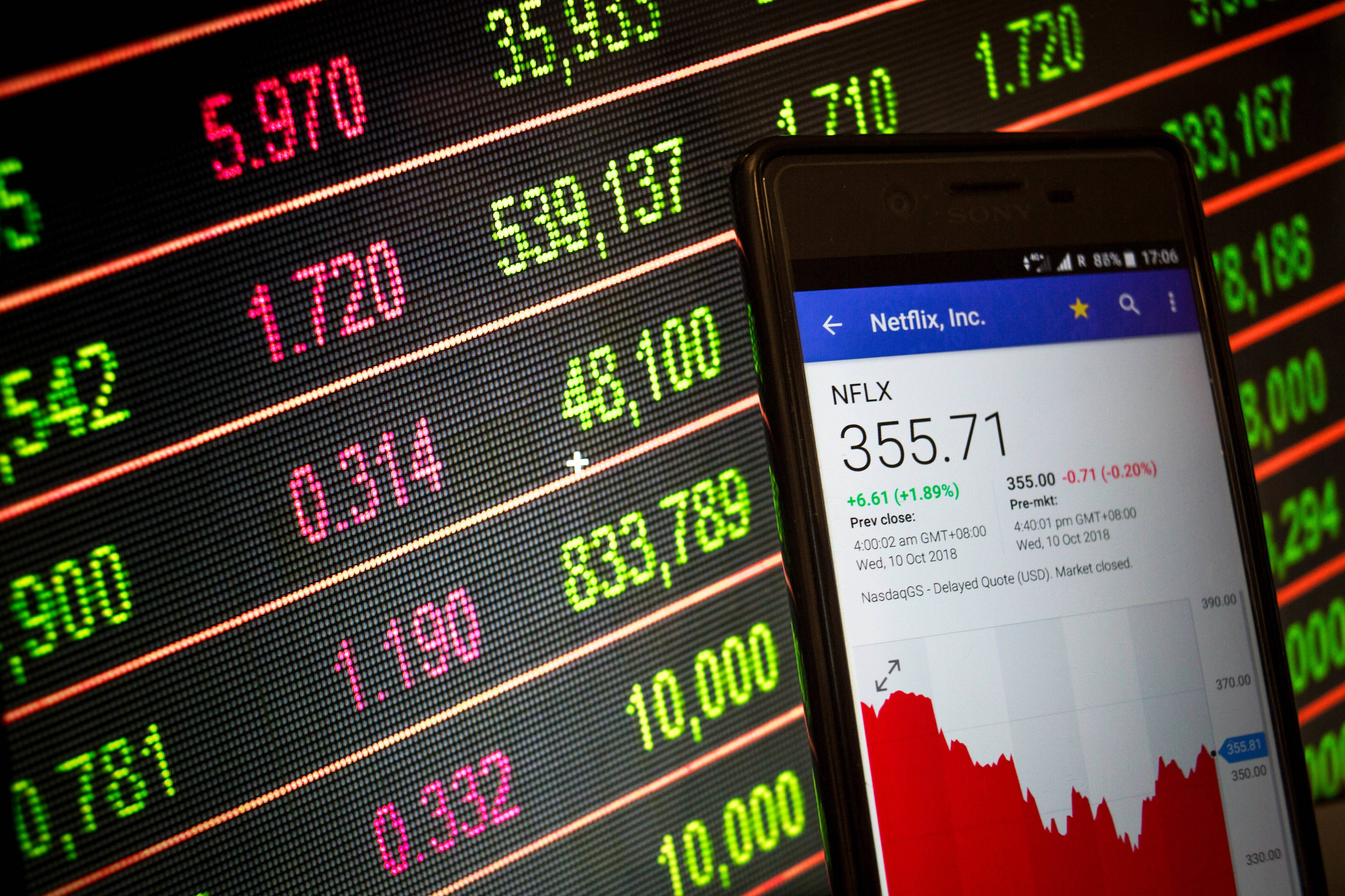 A smartphone displays the Netflix, Inc. market value on the