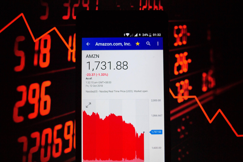 A smartphone displays the Amazon.com, Inc. market value on