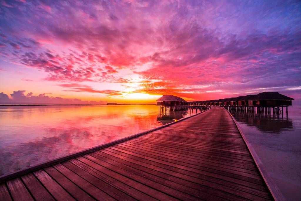 island, water villas resort. Beautiful sky and clouds. Beautiful beach background for summer travel with sun, beach wooden jetty. Summer mood sun beach background concept.