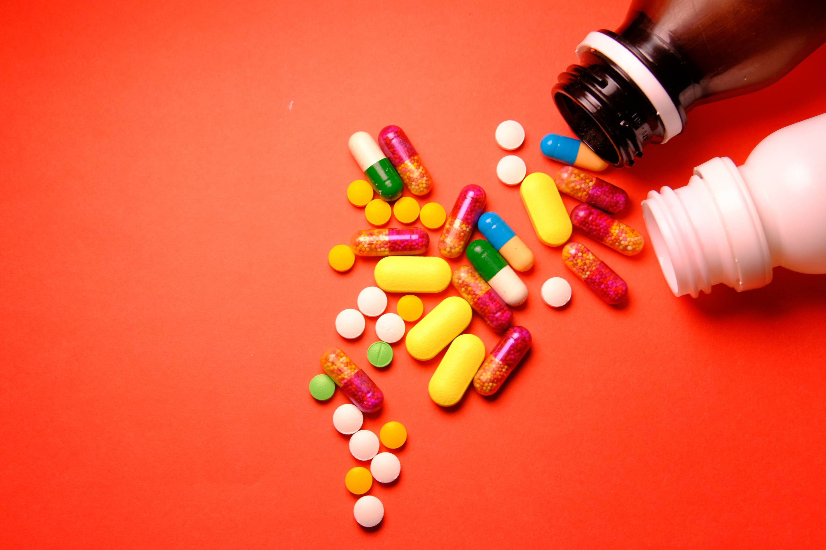colourful pills spilled on red background.