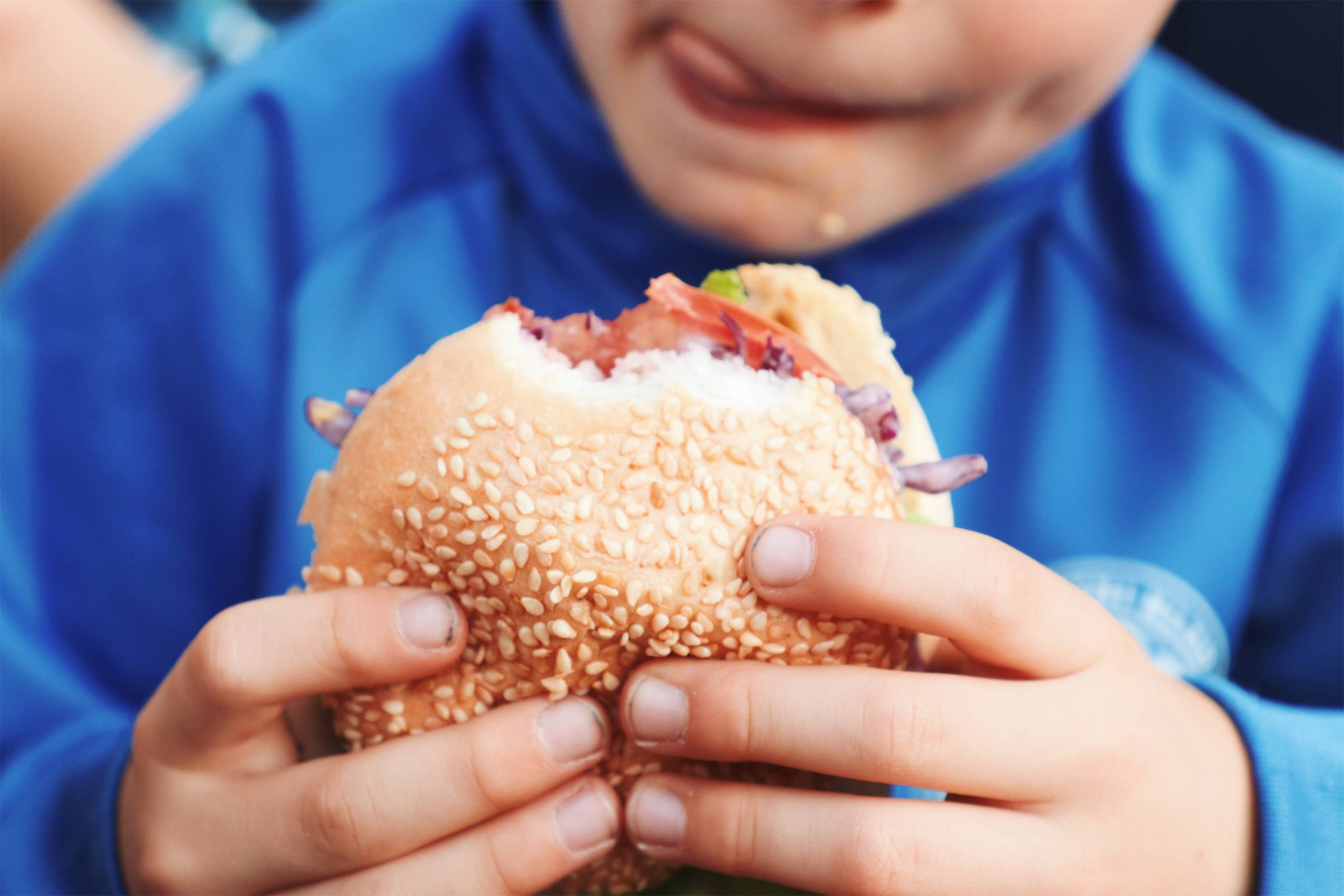 Midsection Of Boy Holding Burger
