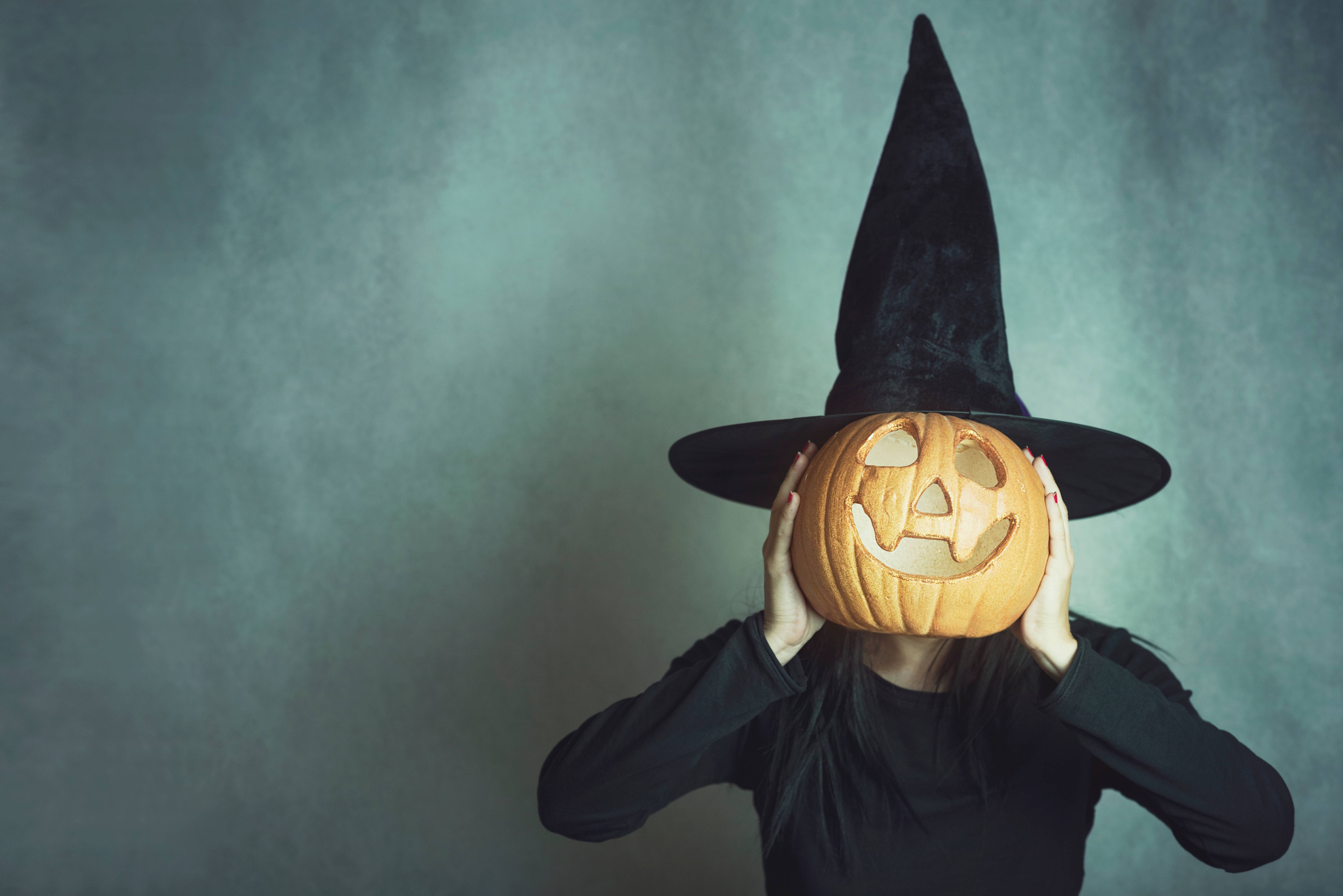 Woman Wearing Costume Covering Face With Jack O Lantern Against Wall During Halloween