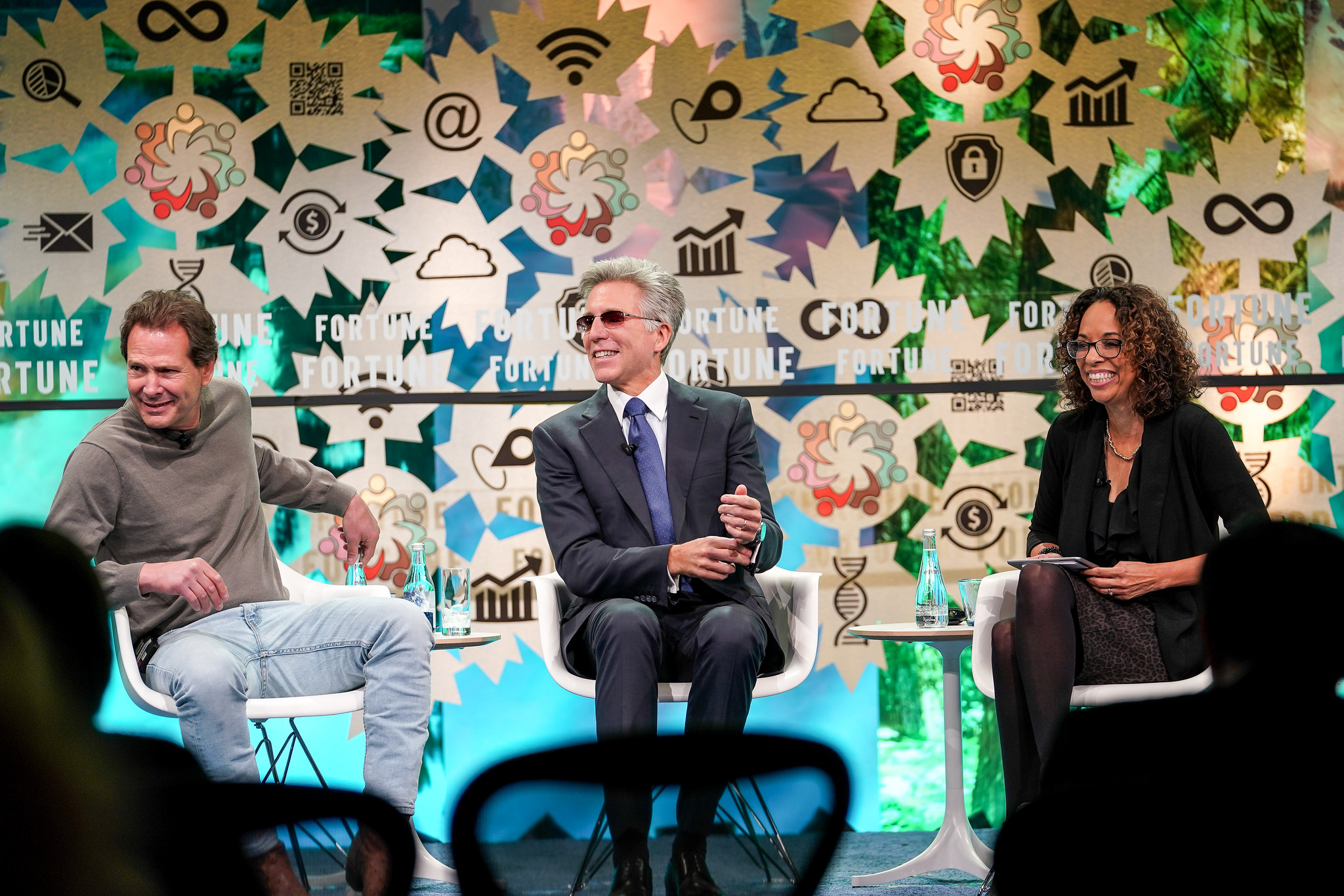 Dan Schulman (left), Bill McDermott (center), and Ellen McGirt (right) sit on stage laughing at Fortune's Global Forum.