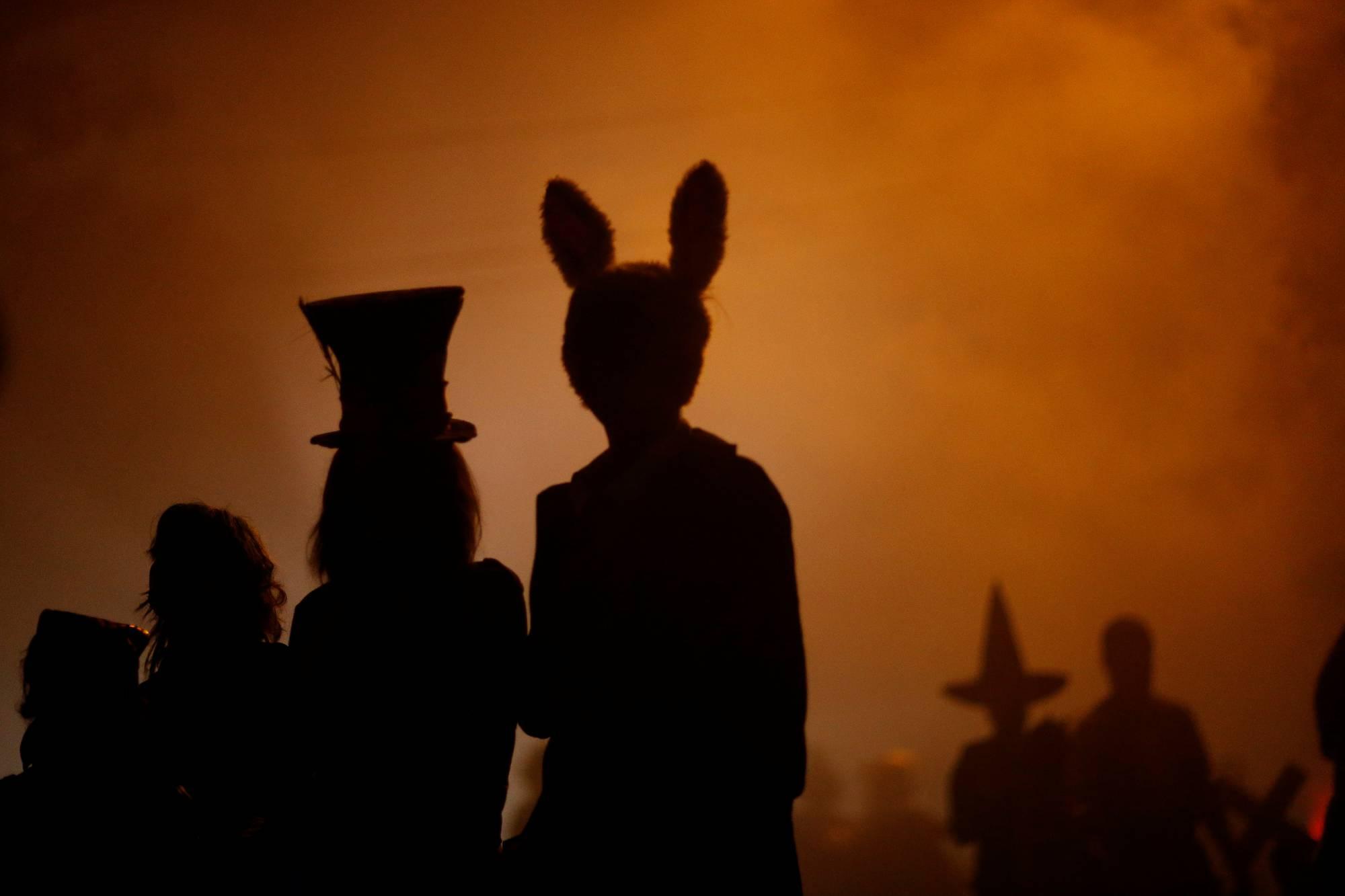People wearing costumes walk during Halloween in Sierra Madre