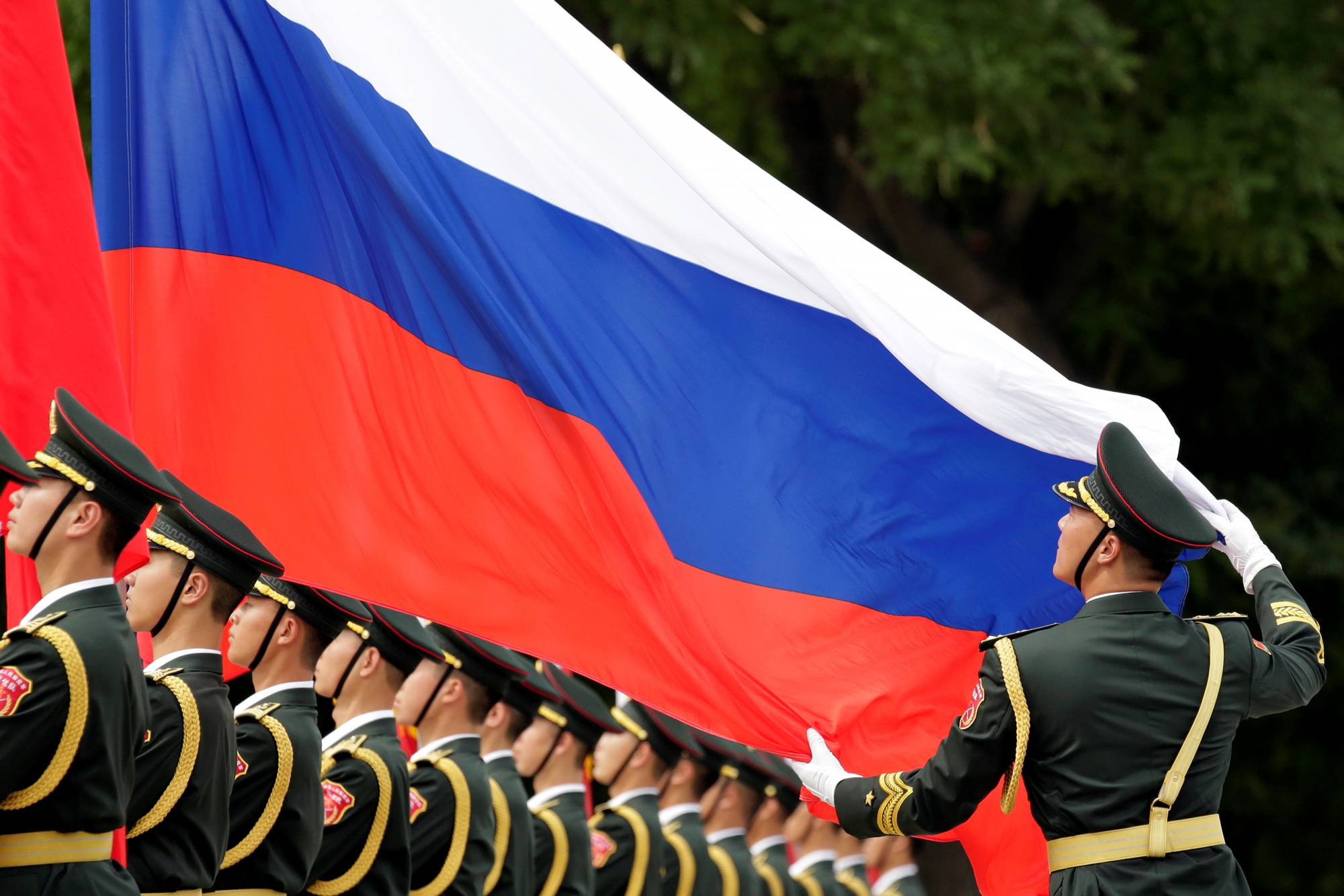 An honour guard holds a Russia flag during preparations for a welcome ceremony for Russian President Vladimir Putin outside the Great Hall of the People in Beijing, China