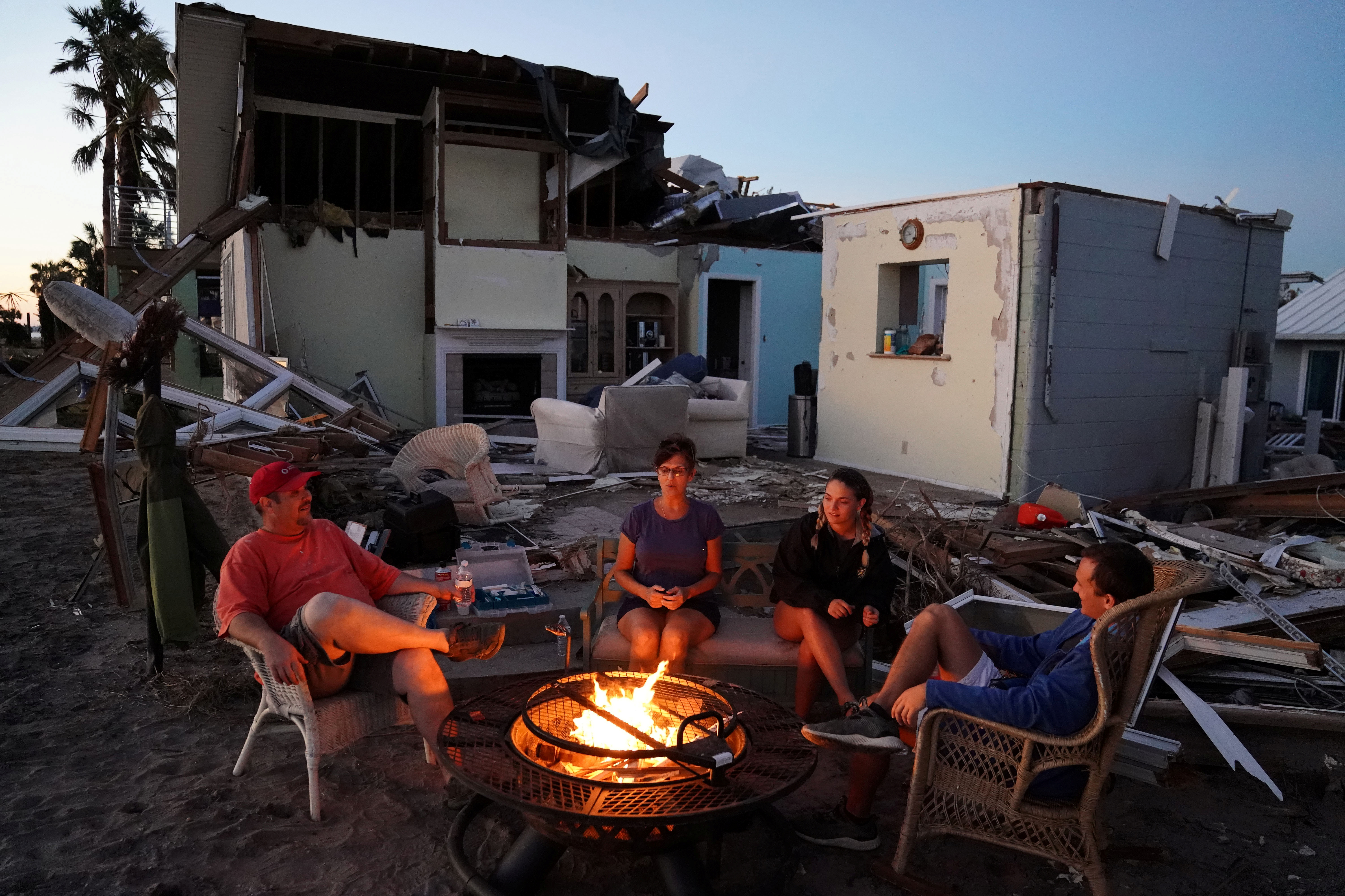 A family sits by a fire and prepares to eat a dinner of MREs in front of their house with no roof following Hurricane Michael in Mexico Beach, Florida