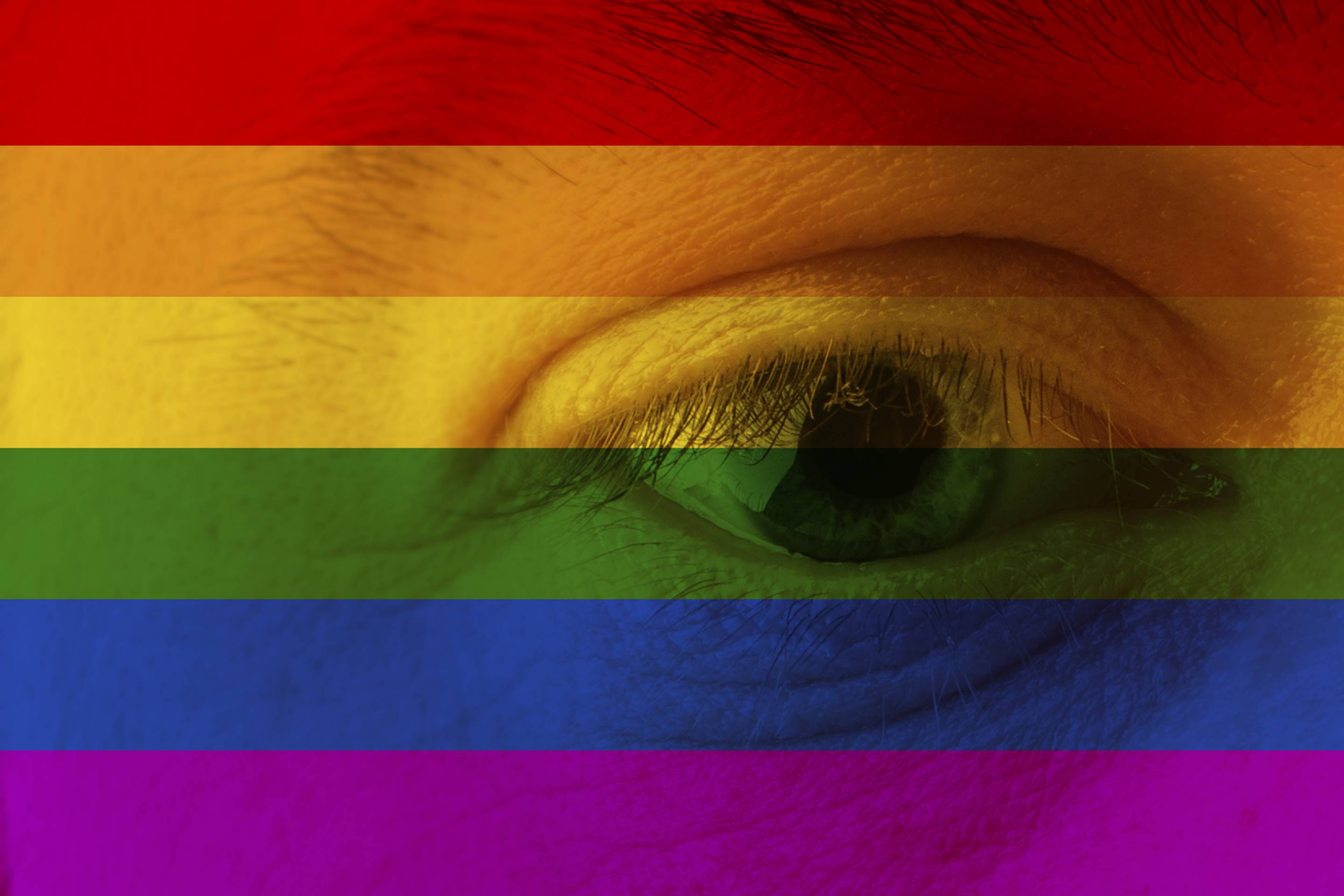 Human face and eye painted with flag of LGBT movement