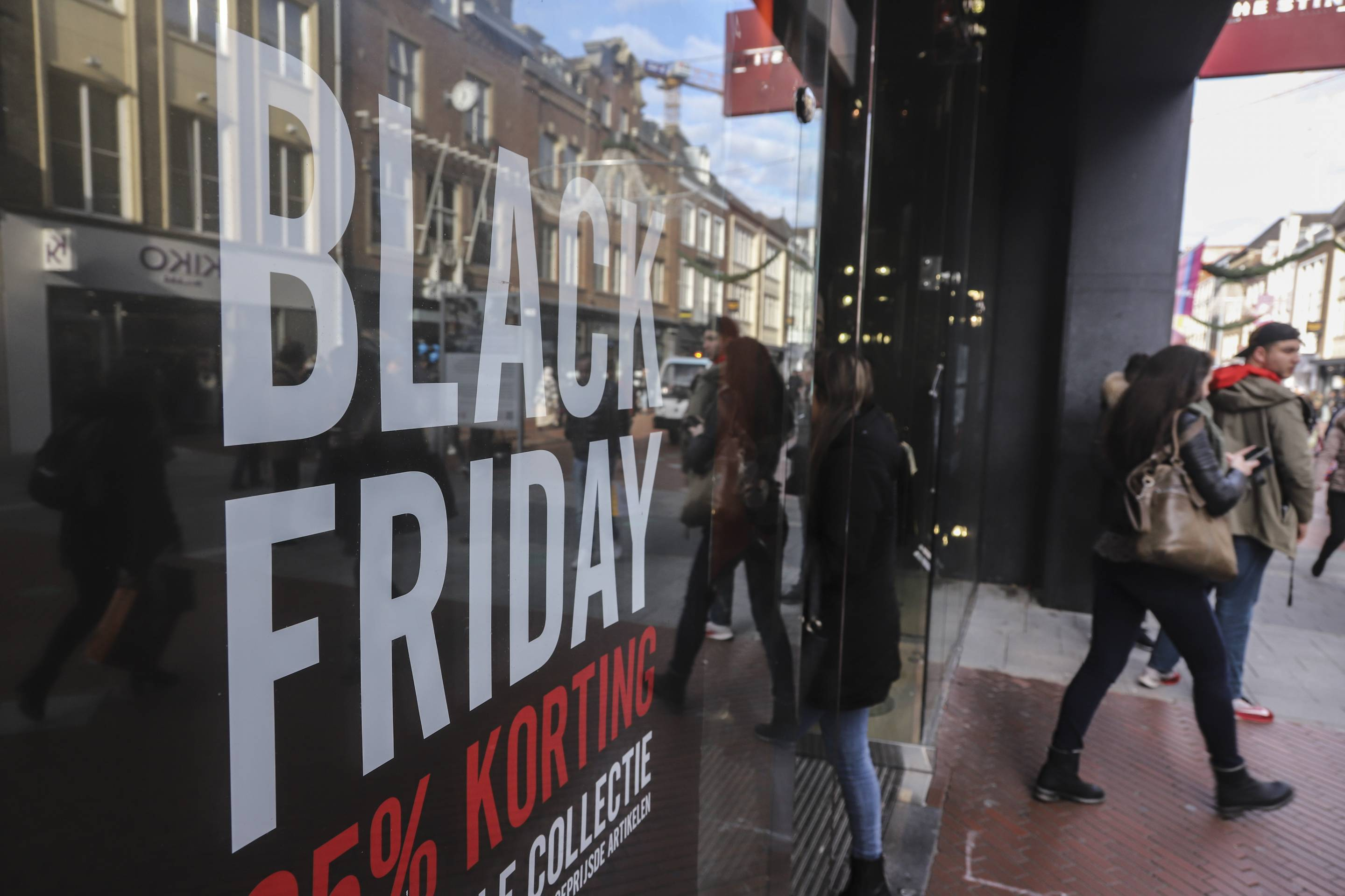 People seen walking by a Black Friday signs with discounts