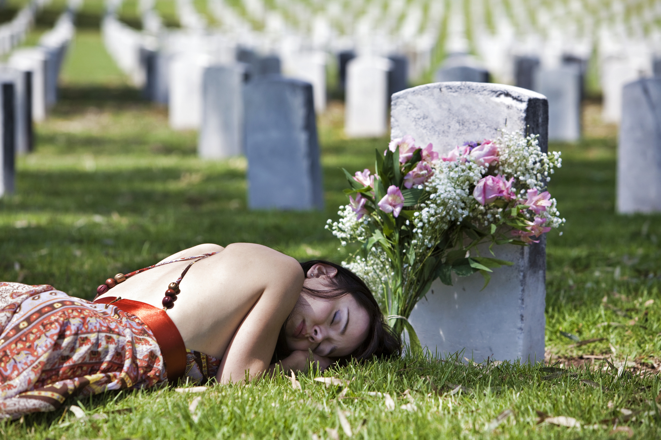 Mourning woman lying down by grave marker