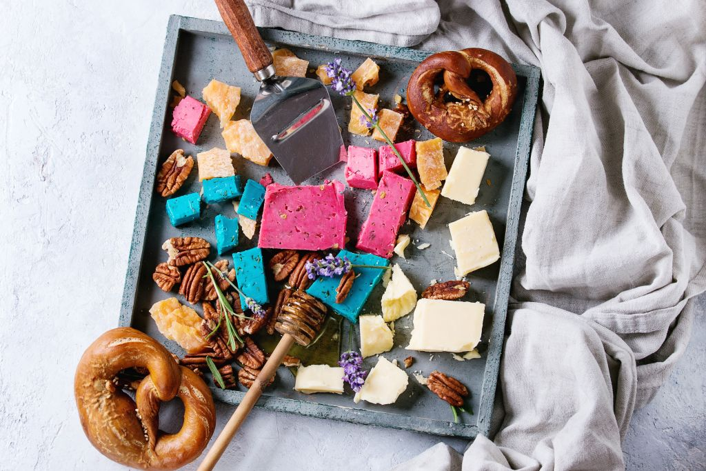 Variety of colorful holland cheese traditional soft, old, pink basil, blue lavender served with pecan nuts, honey, lavender flowers, pretzels bread on wood tray over gray texture background. Flat lay