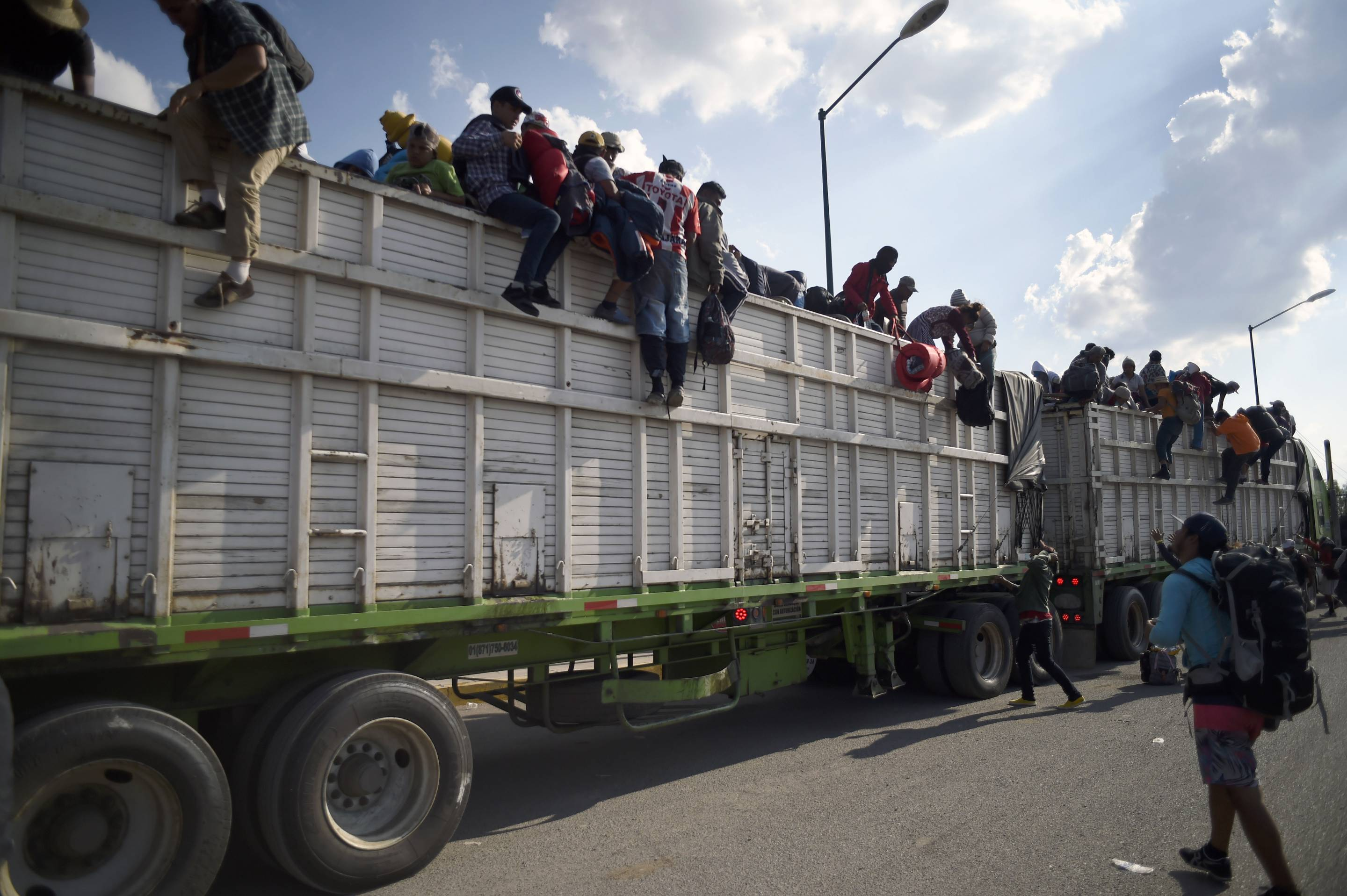 Central American migrants descend from a truck at a temporary shelter in Irapuato, Mexico, on Nov. 11, 2018.