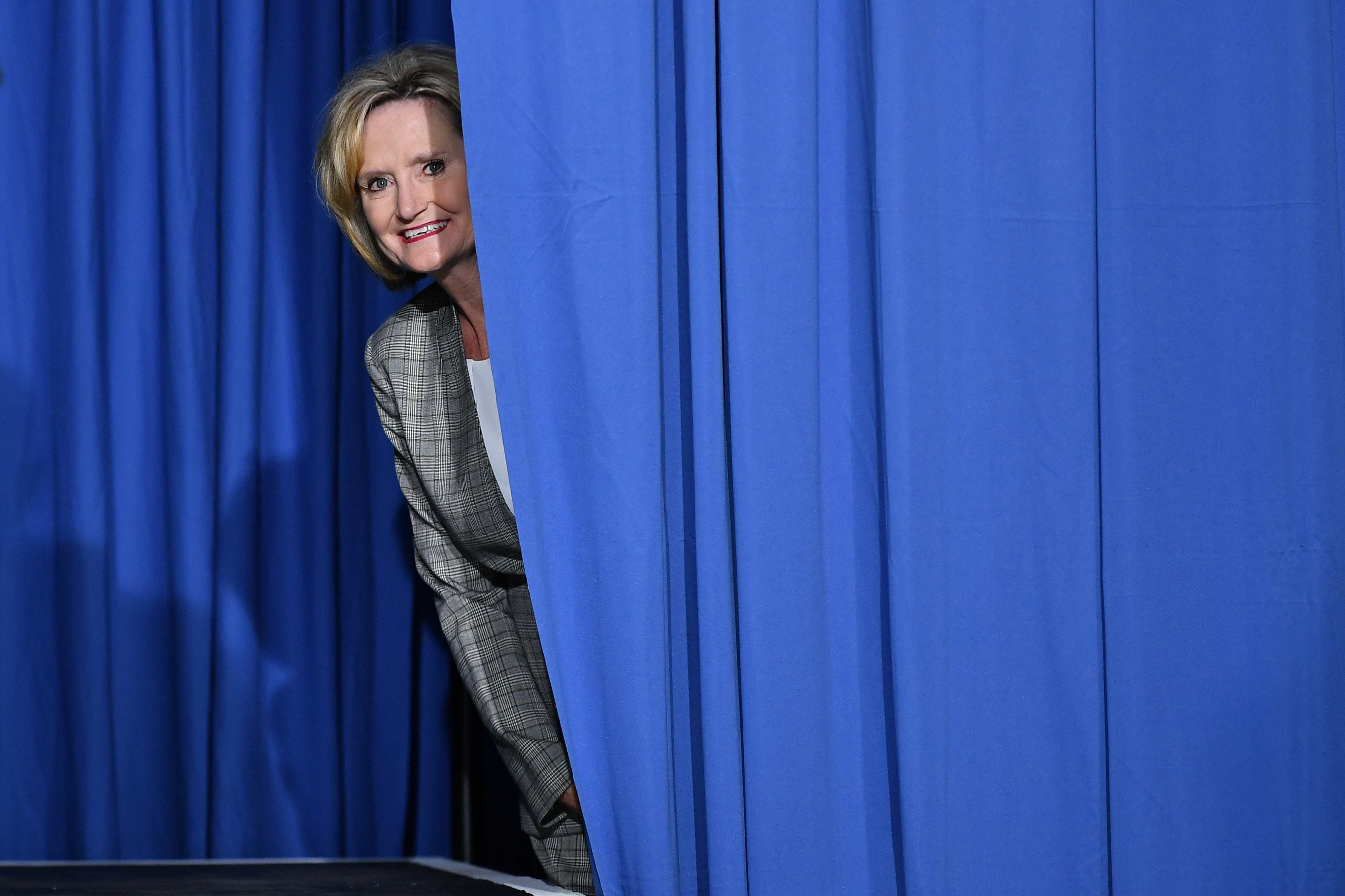 Senator Cindy Hyde-Smith peaks out from behind a curtain before a rally with US President Donald Trump at Landers Center Ð Arena in Southaven, Mississippi, on October 2, 2018
