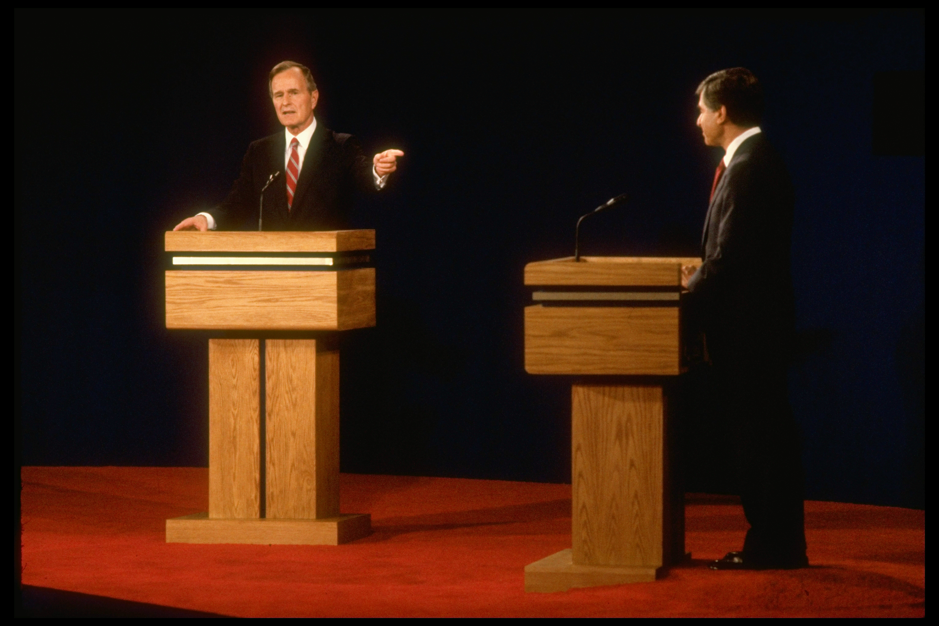 Democratic presidential candidate Michael Dukakis poised podium-side, facing his point-making Republican opponent VP George Bush (L) in first debate.