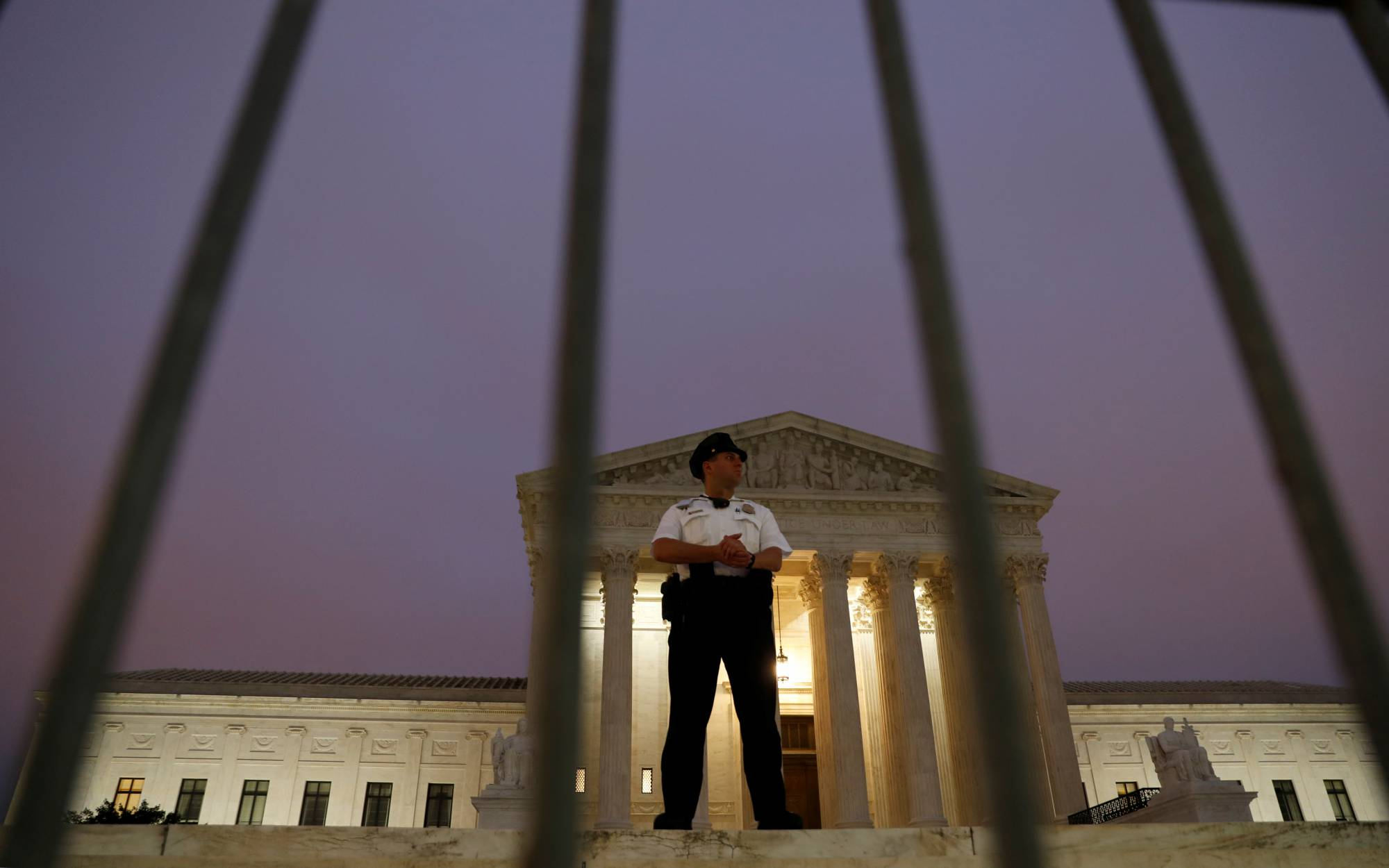 Lone U.S. Supreme Court officer guards the steps of the court after Justice Kavanaugh was sworn in as a justice inside in Washington