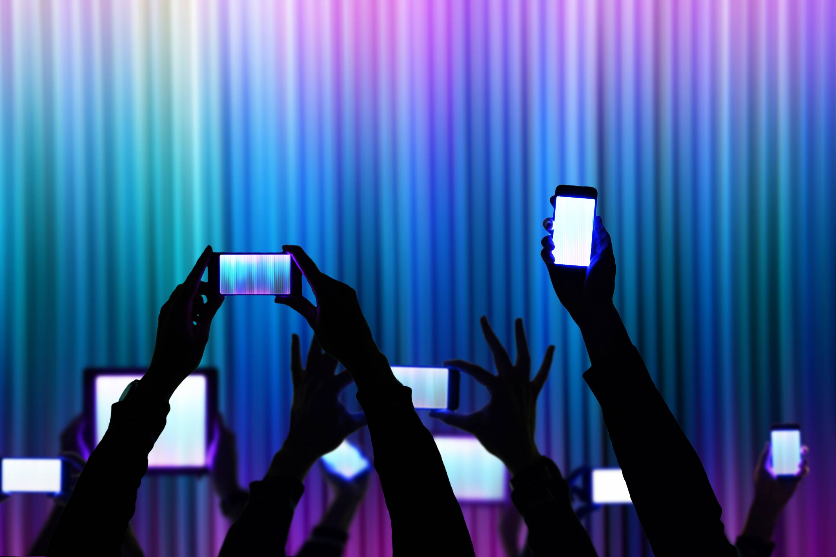People raise his bright smartphone and tablet device during a night show celebration with dark silhouettes and colorful background.