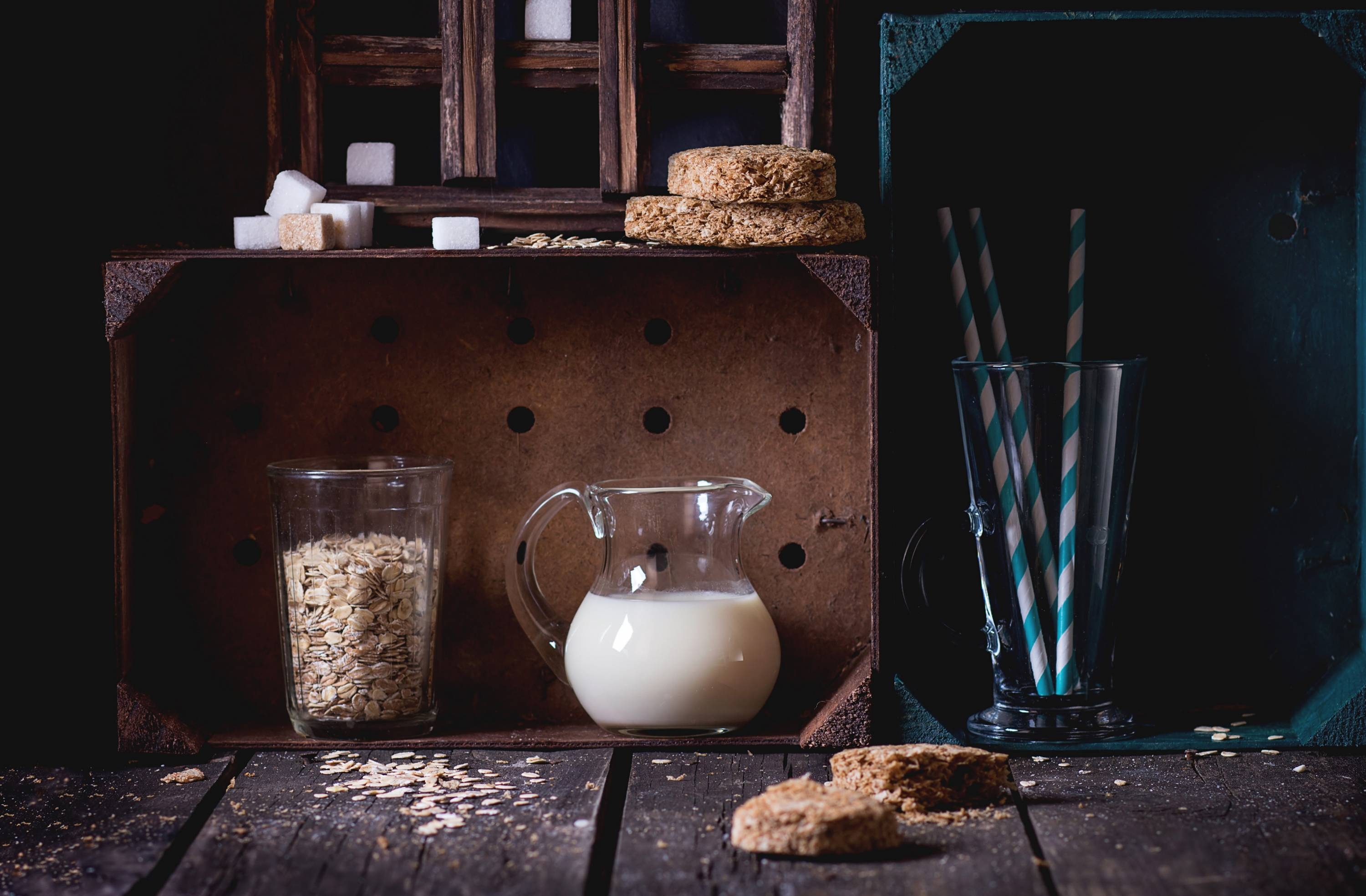 Glass jug of non-dairy oat milk and retro glass of oat flakes with sugar cubes and crispbread in wooden kitchen cabinet over old wooden table. Dark rustic style.
