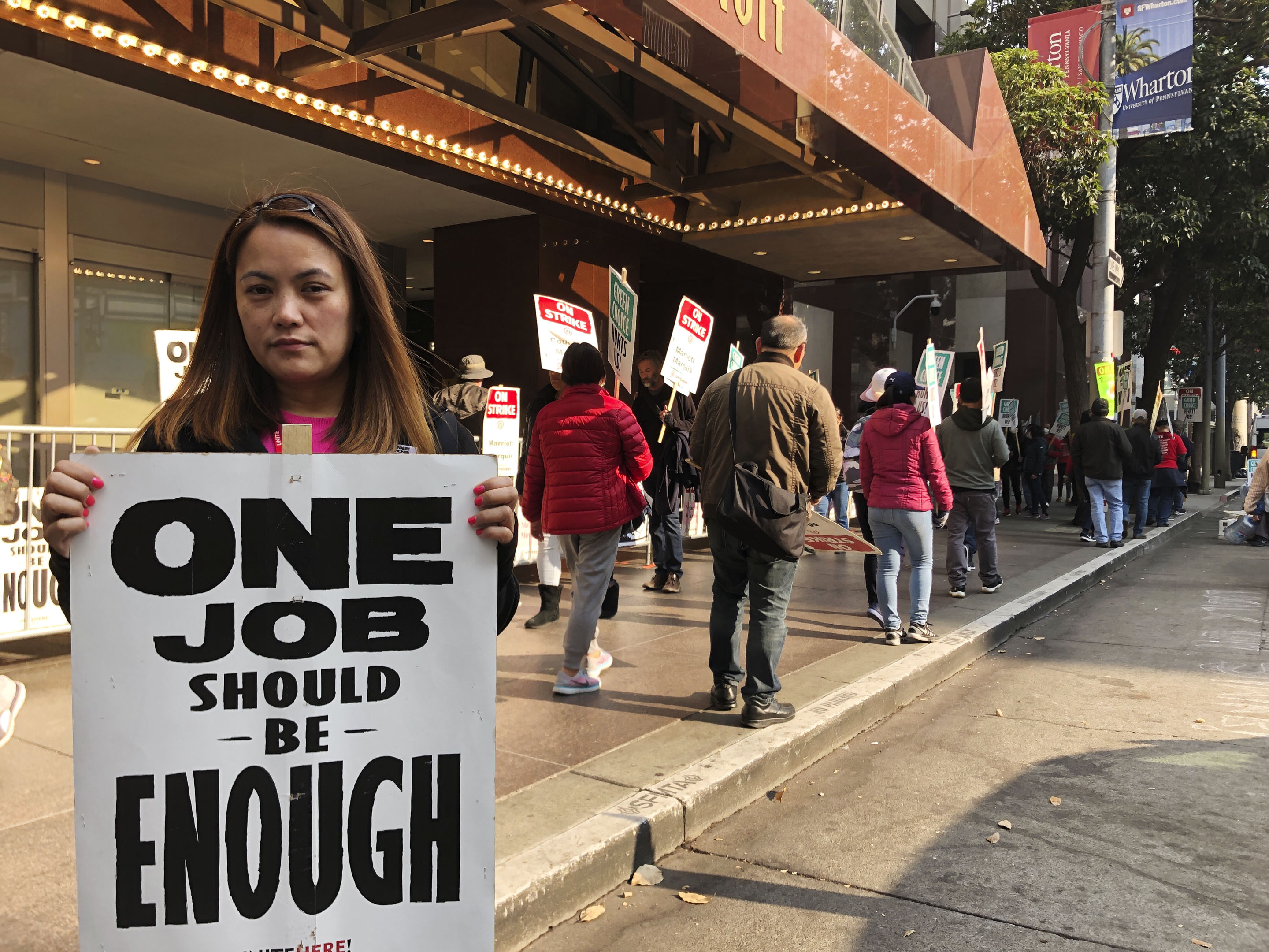 Larrilou Carumba walks the picket line in front of the San Francisco Marriott Marquis. The new contract includes a wage increase.