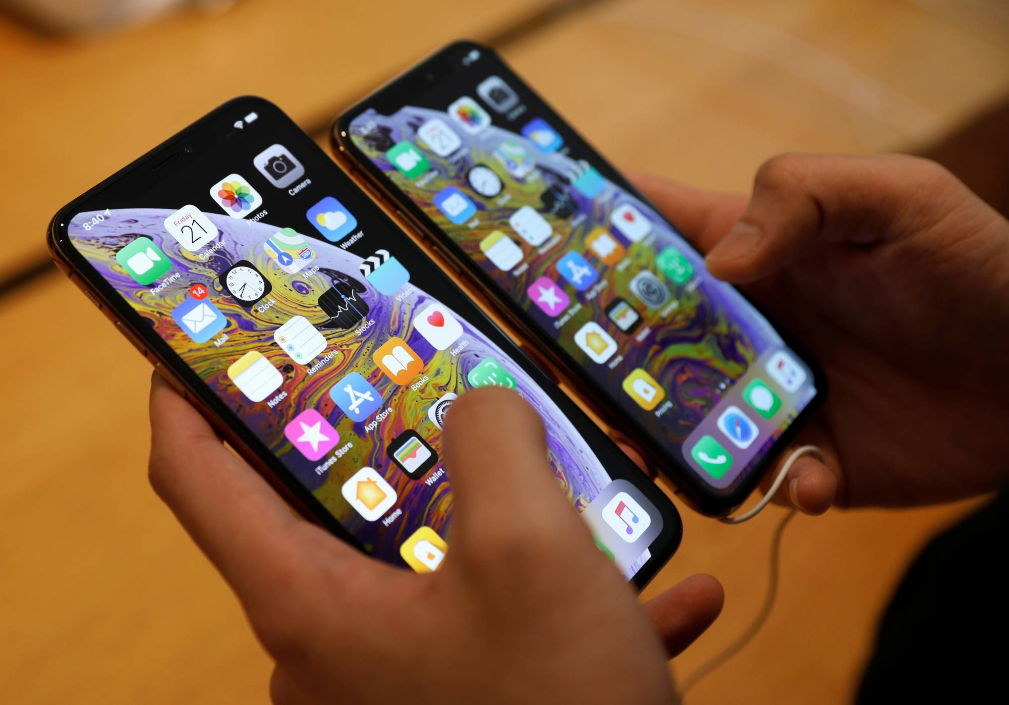 A customer compares the size of the new iPhone XS and iPhone XS Max at the Apple Store in Singapore