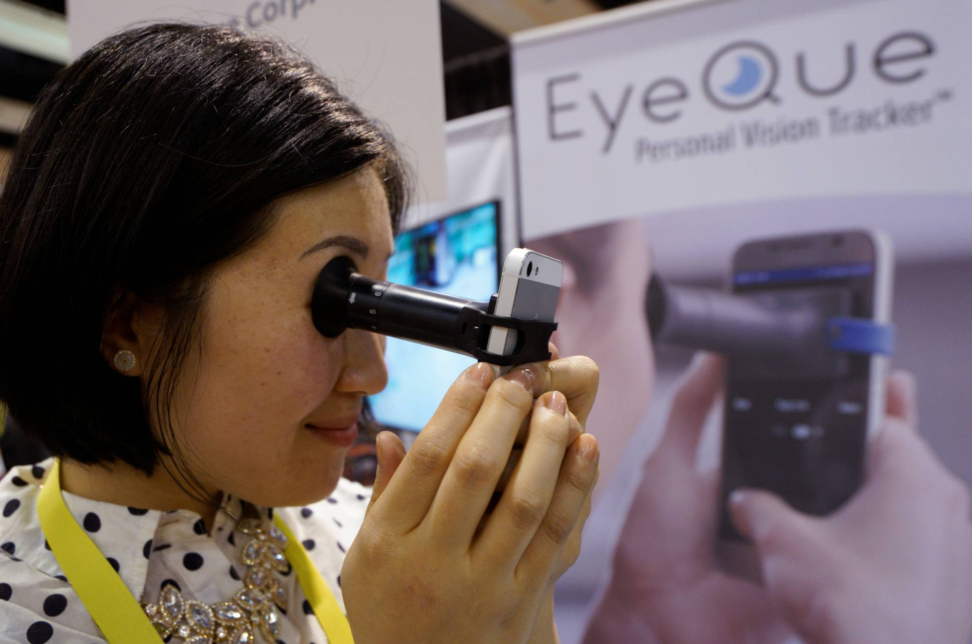 Phoebe Yu of Eyeque Corp., demonstrates her EyeQue vision testing device attached to a smart phone at CES in Las Vegas