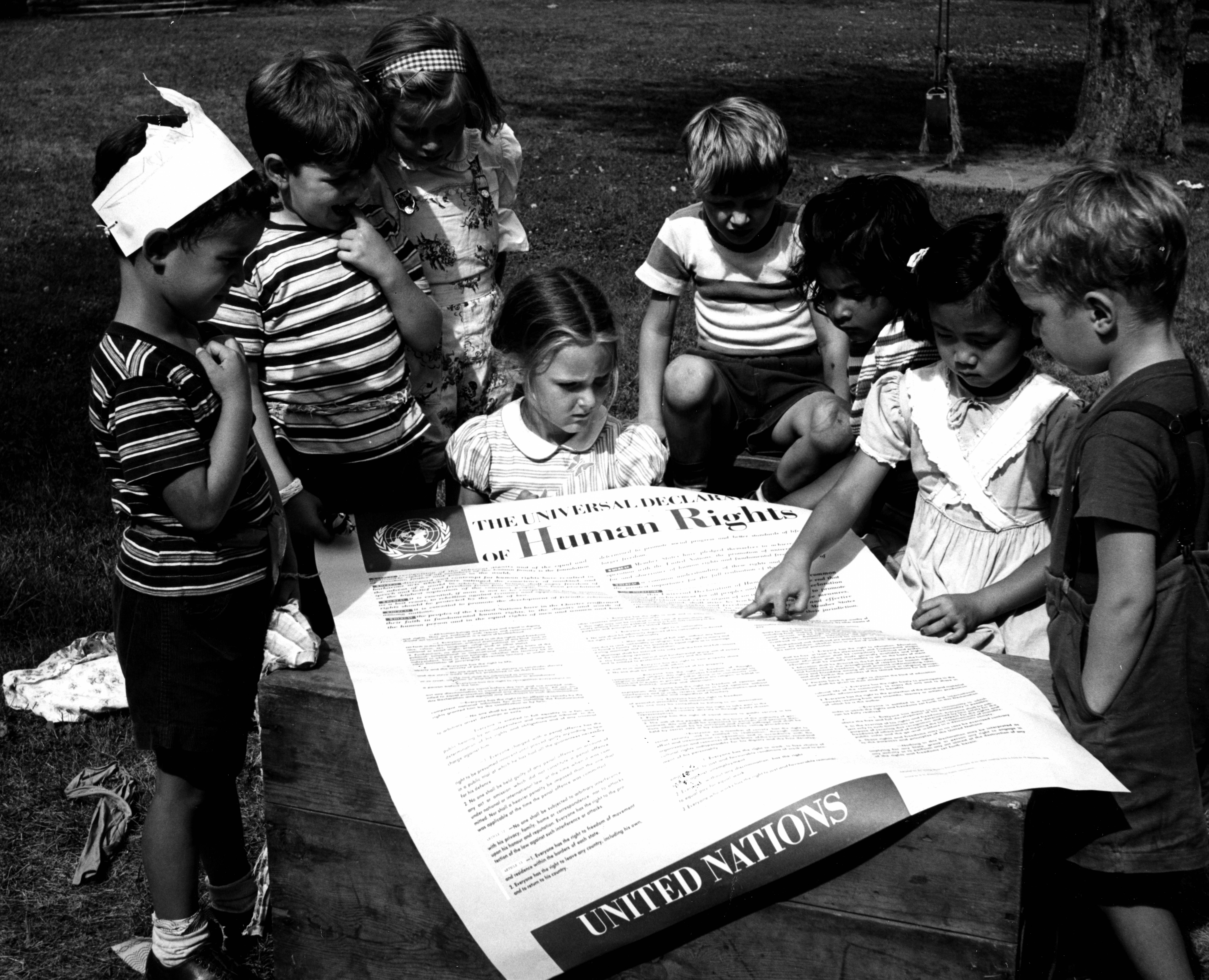A group of school children sit outside, gathered around a large poster printed with the UN's Universal Declaration of Human Rights.