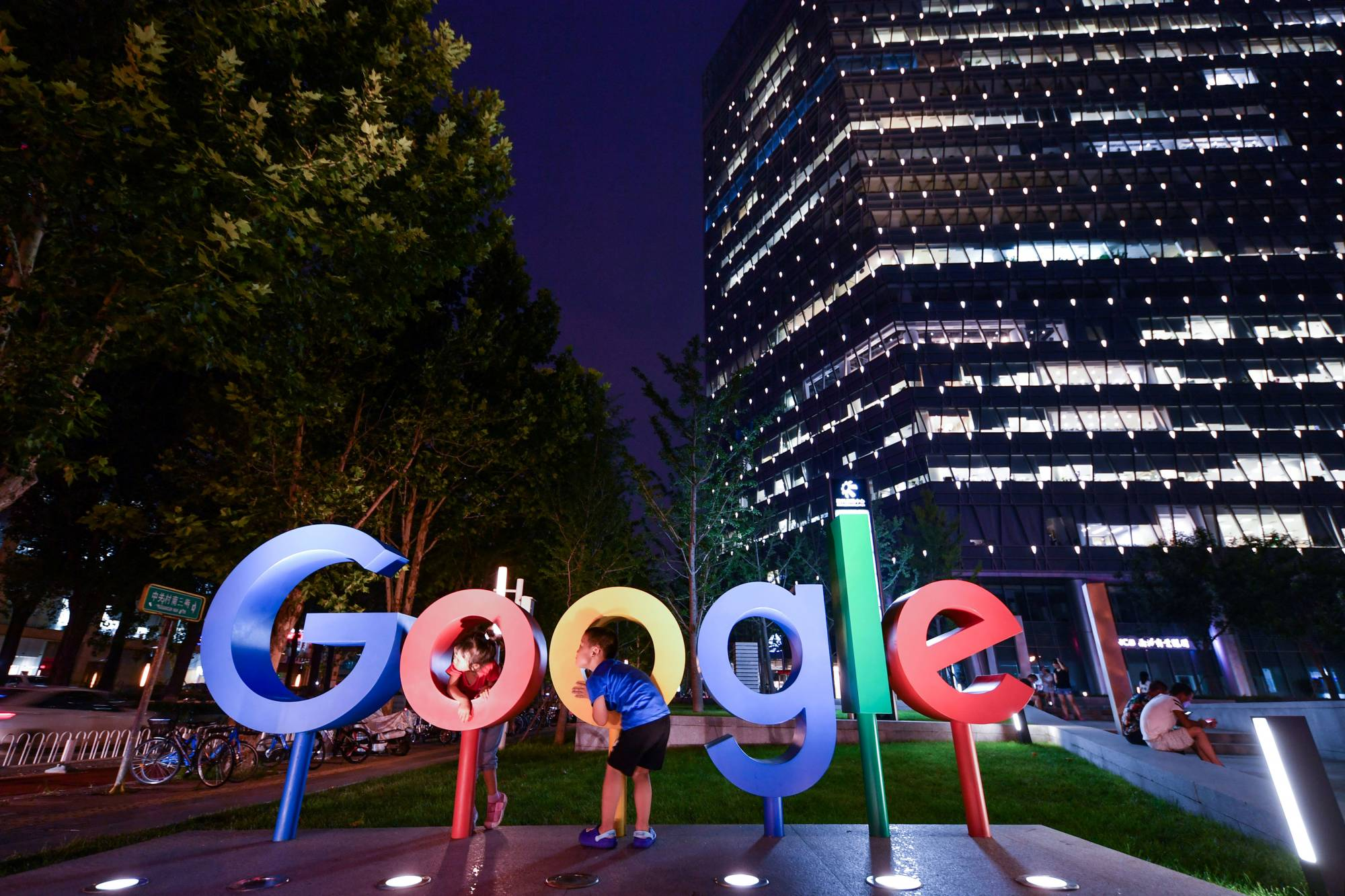 Children play around a sign of Alphabet Inc's Google outside its office in Beijing