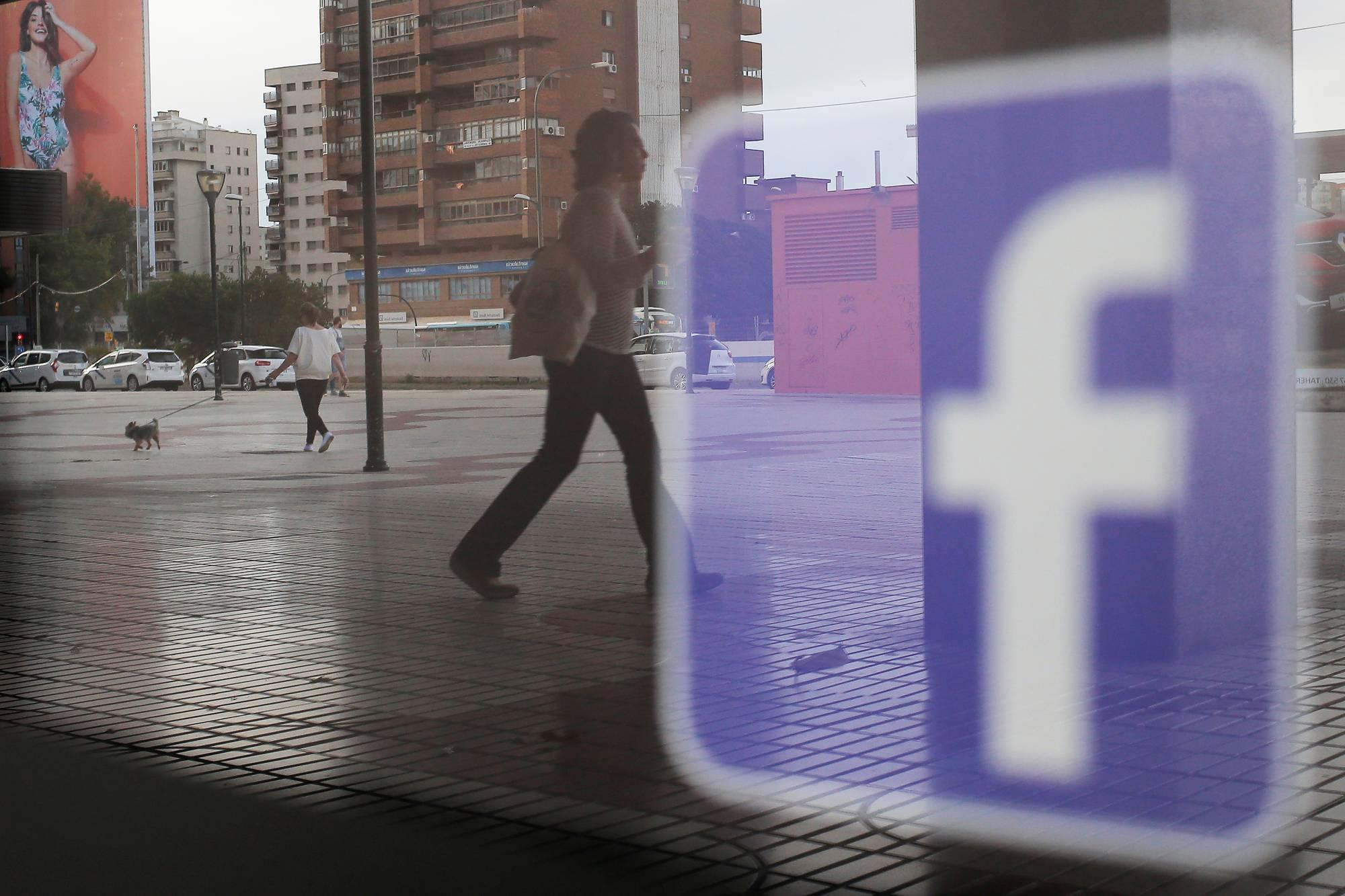 Facebook logo is seen on a shop window in Malaga