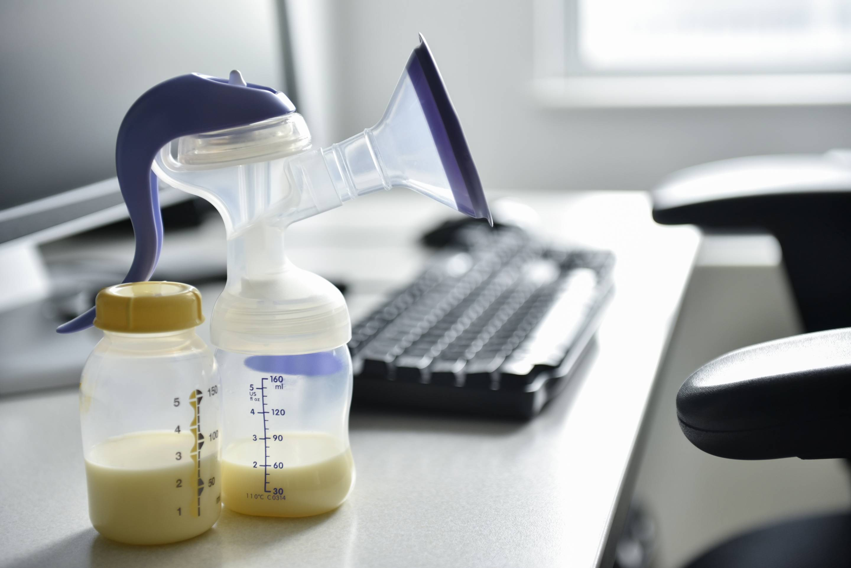 Breast pump and bottle of breast milk near computer