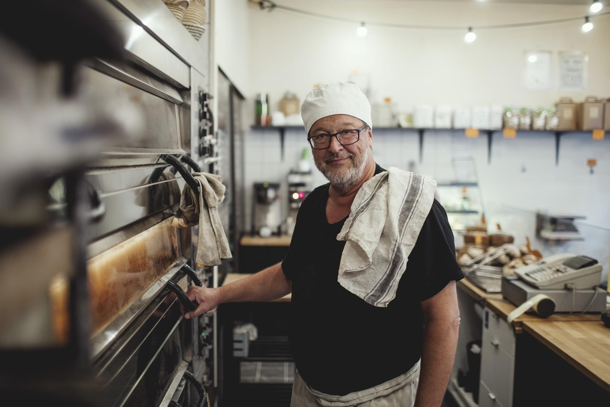 Portrait of senior baker standing by oven at bakery