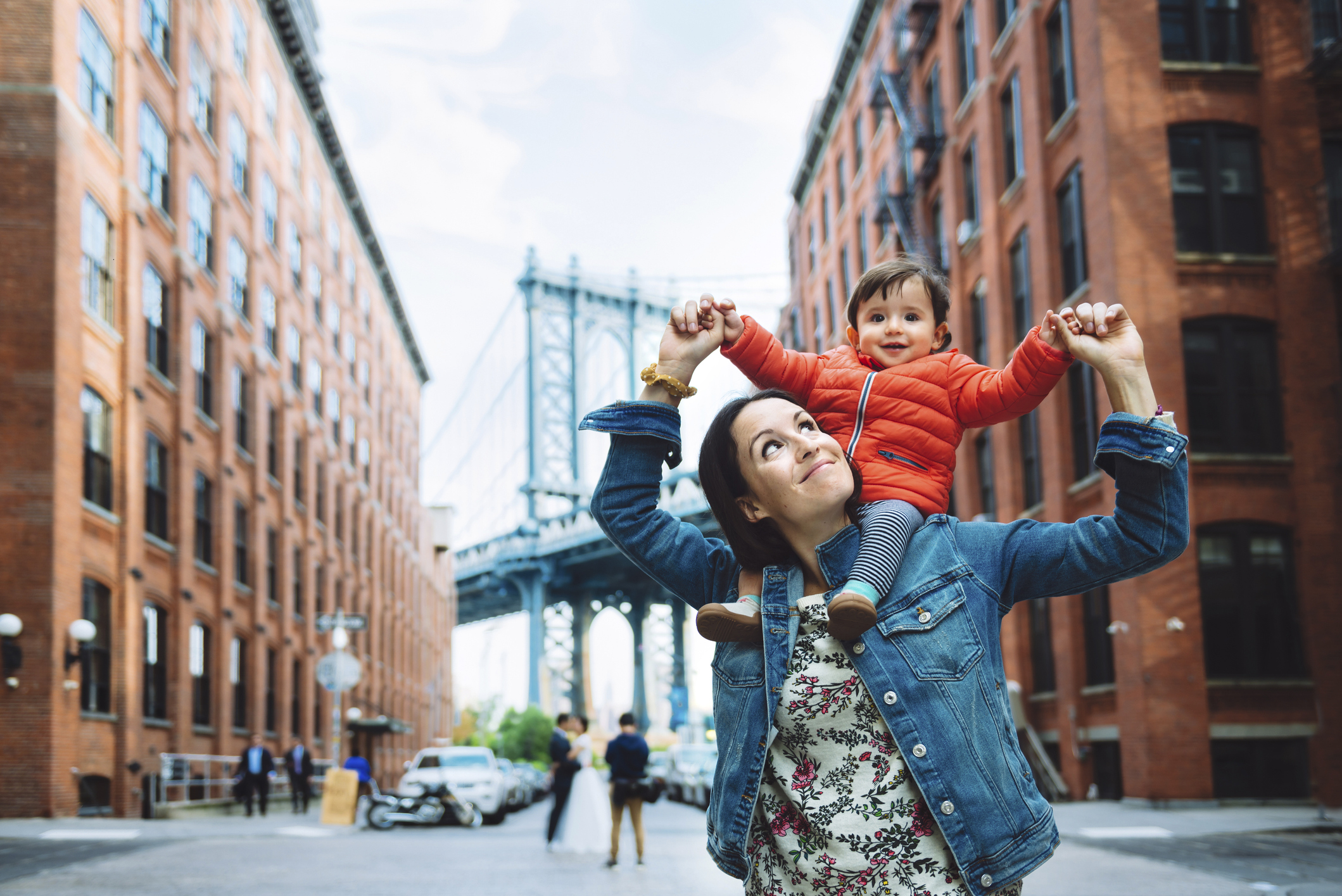USA, New York, New York City, Mother and baby in Brooklyn with Manhattan Bridge in the background