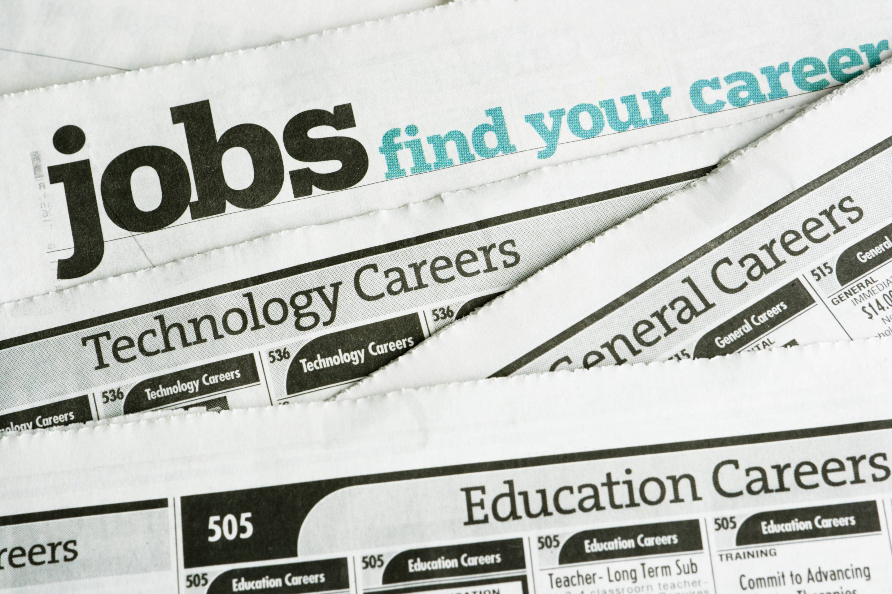 Newspaper job listing pages are stacked to illustrate the job search and the job hunting process.