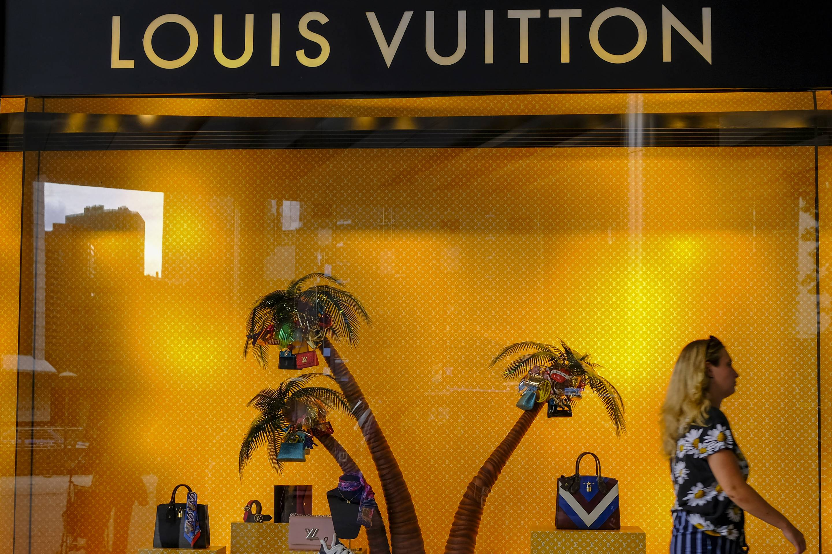 A lady seen passing by a Louis Vuitton boutique