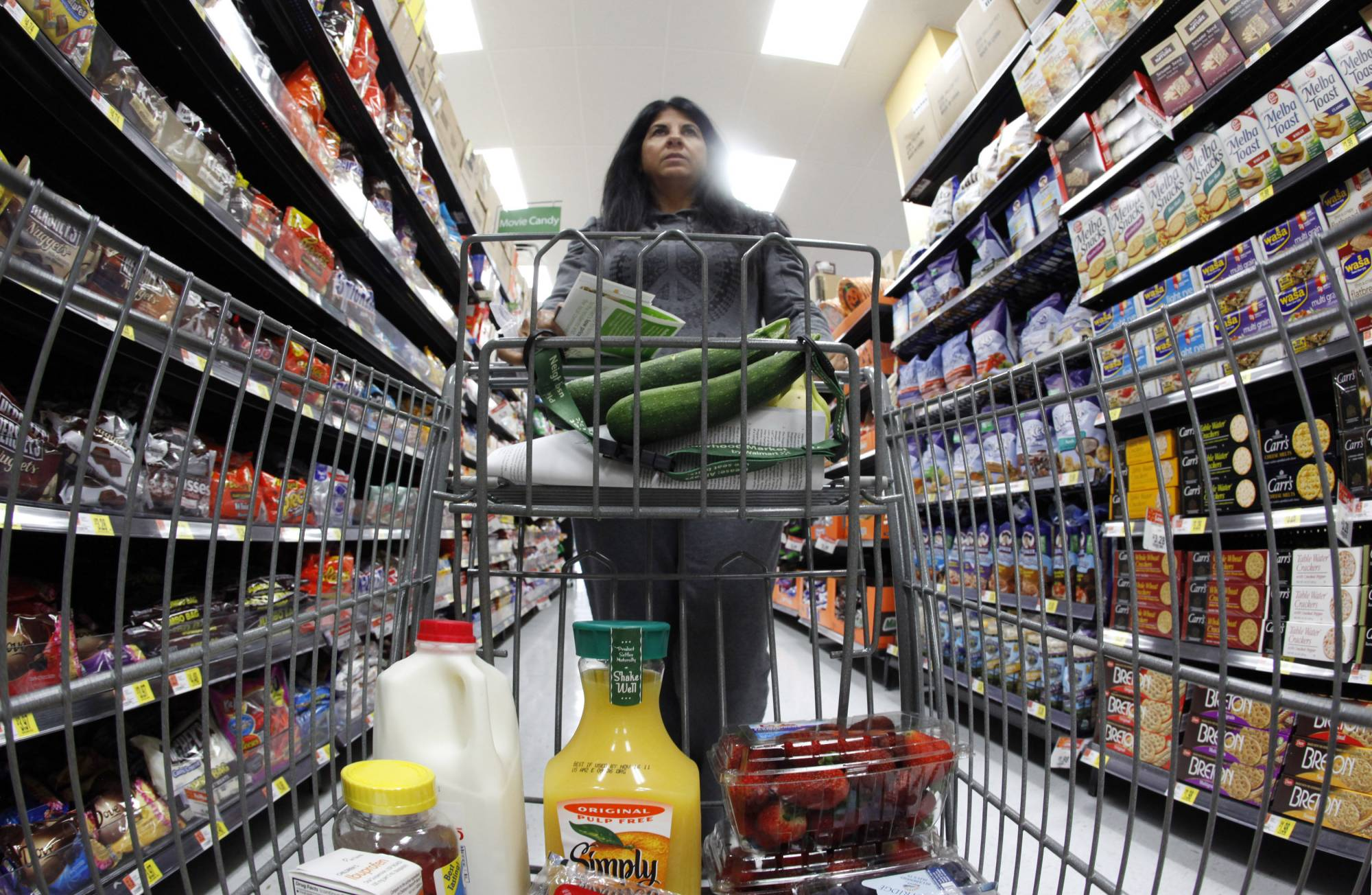 A shopper walks down an aisle in a newly opened Walmart Neighborhood Market in Chicago