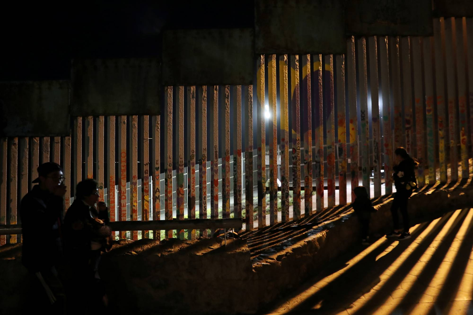 People in silhouette are seen in front of the U.S. and Mexico border fence at Friendship Park in Tijuana, Mexico
