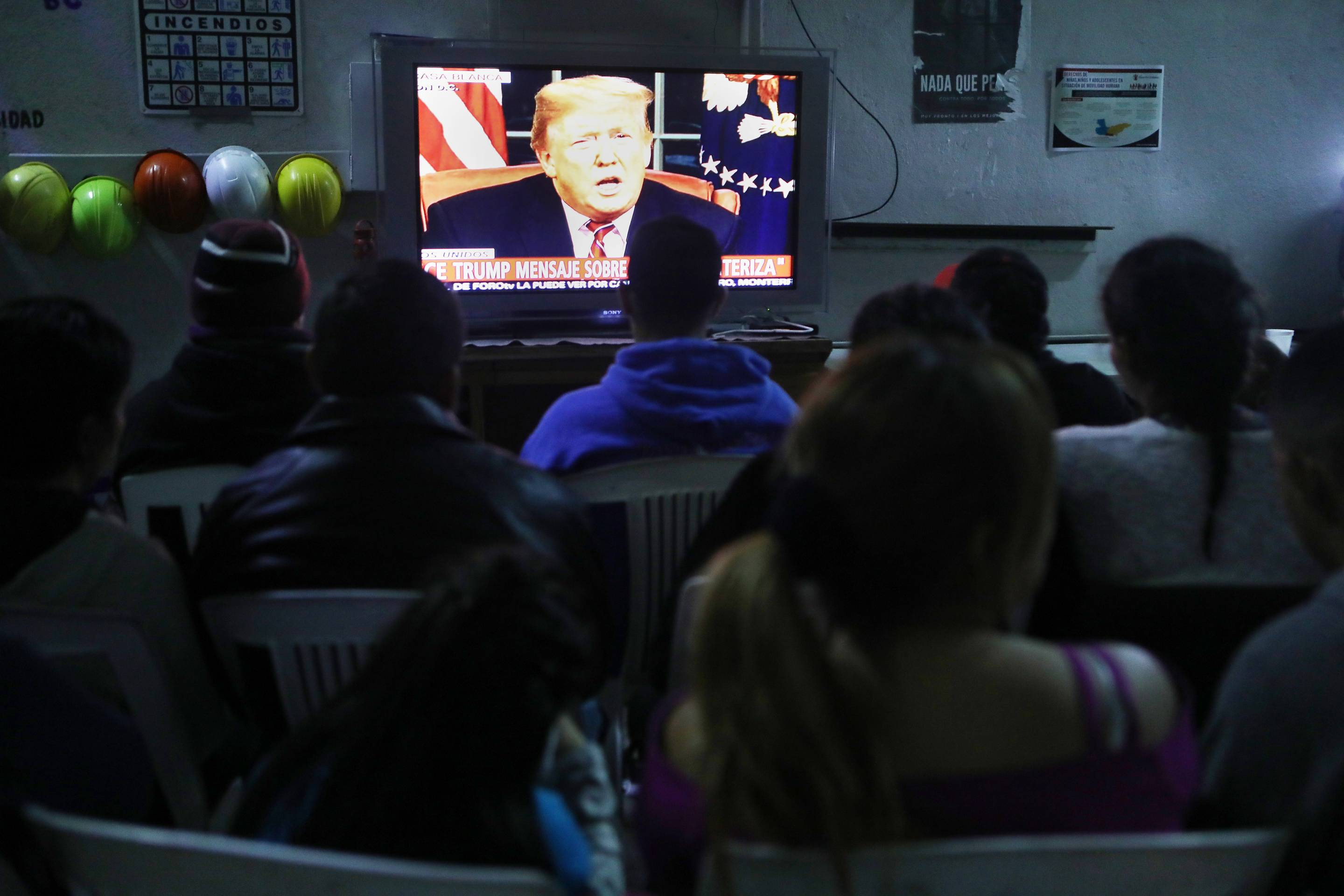 Migrants view a live televised speech by President Donald Trump on border security at a shelter on Jan. 8, 2019 in Tijuana, Mexico.