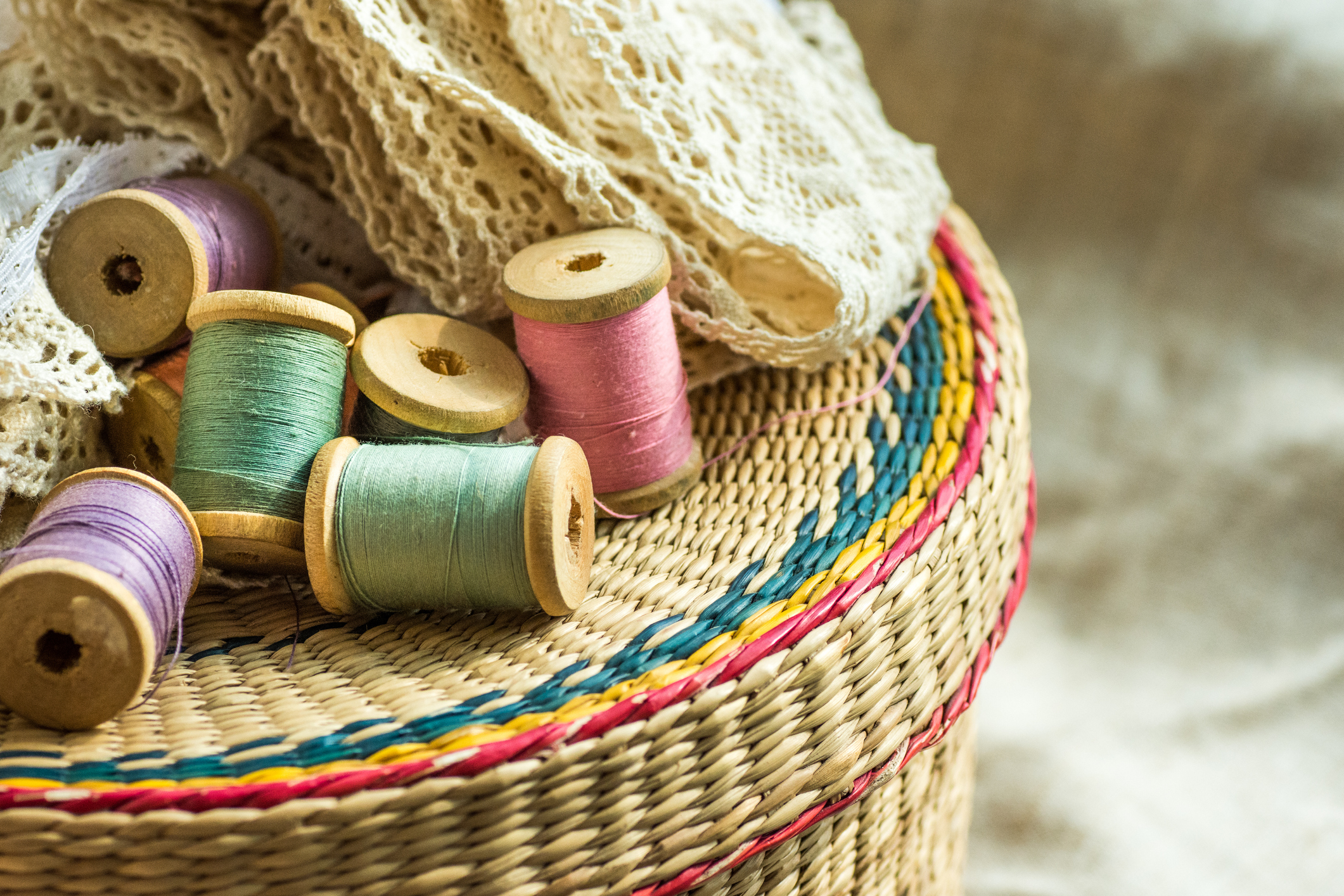 Woven rattan crafts and sewing supply box, wooden spools, rolls of lace, linen cloth background, hobby fashion concept