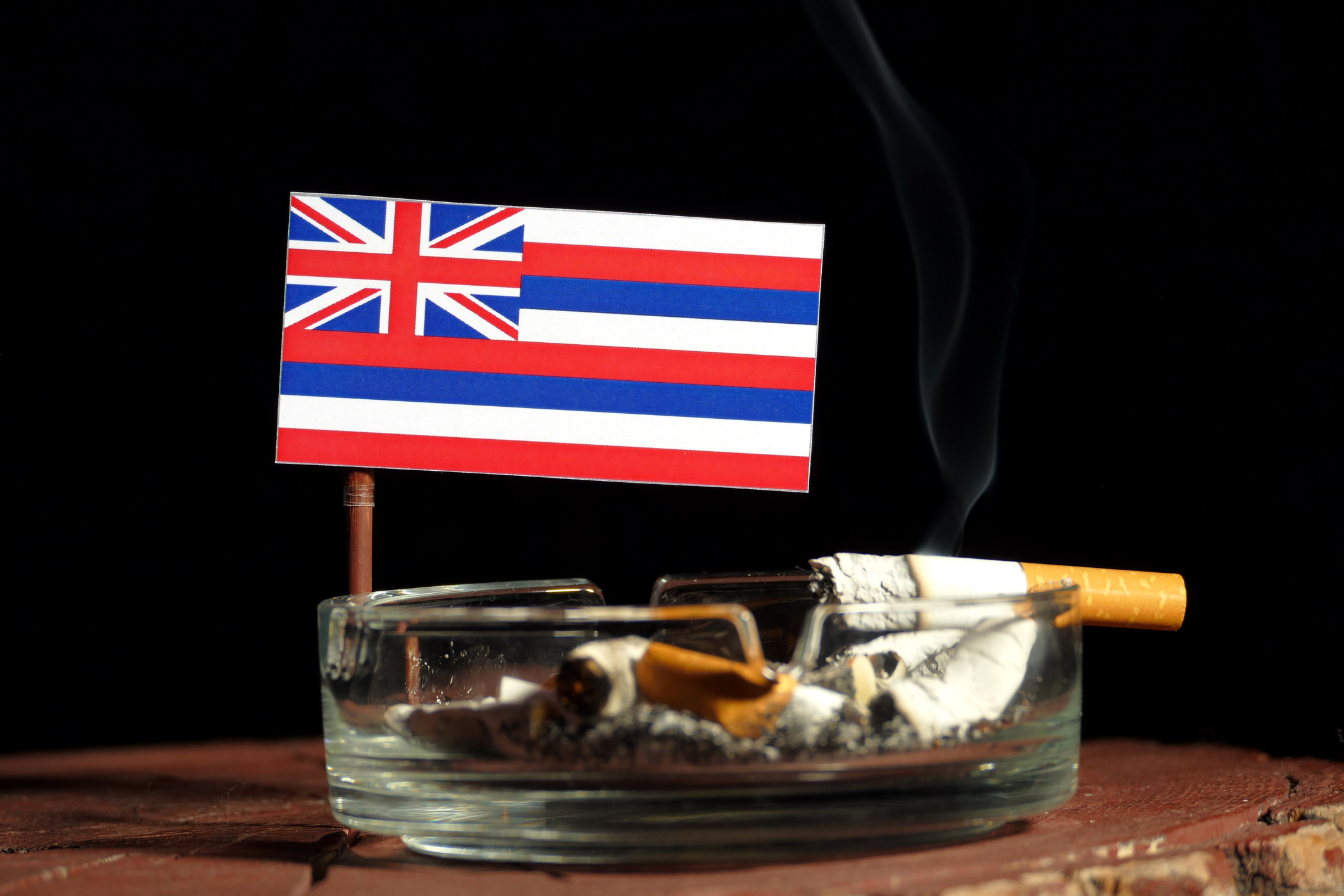 Hawaii flag with burning cigarette in ashtray isolated on black background