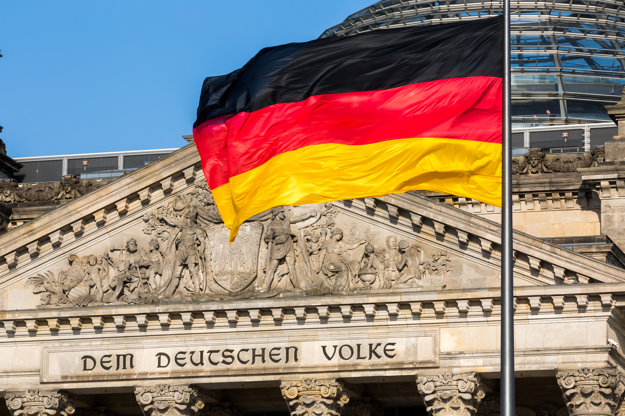 "The famous inscriptionon the west portal of the Reichstag building in Berlin: ""Dem Deutschen Volke"" with german flag"