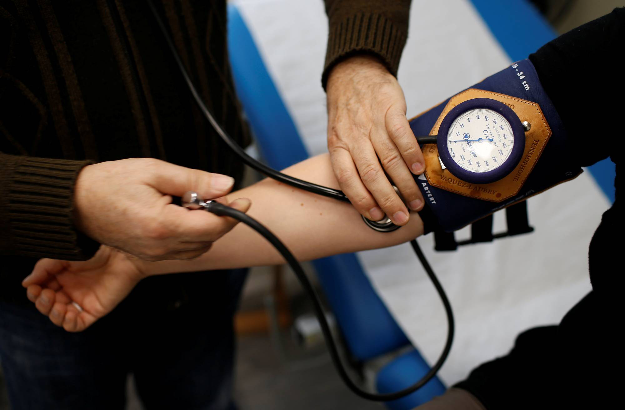 Retired French doctor Jean-Francois Rechner, 67, measures the blood pressure of a patient during a consultation at the 'Service Medical de Proximite' clinic in Laval