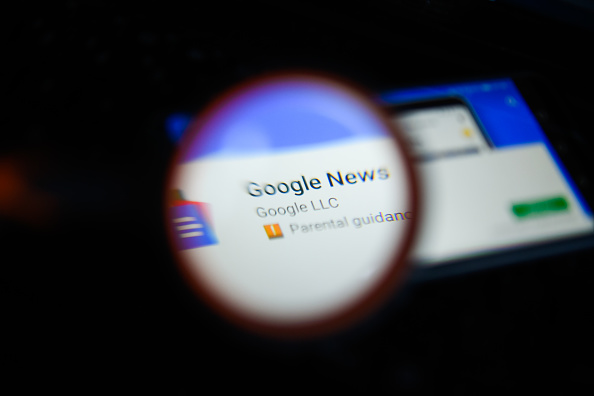 Google News app is seen trough a magnifying glass on an