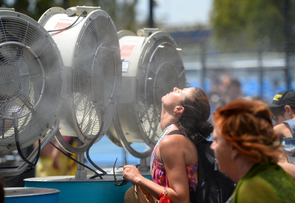 A woman cools off with fans and mist put out for spectators as a heat wave continues to sizzle on day three of the 2014 Australian Open tennis tournament in Melbourne on January 15, 2014. AFP PHOTO / WILLIAM WESTIMAGE RESTRICTED TO EDITORIAL USE - STRICTLY NO COMMERCIAL USE (Photo credit should read WILLIAM WEST/AFP/Getty Images)