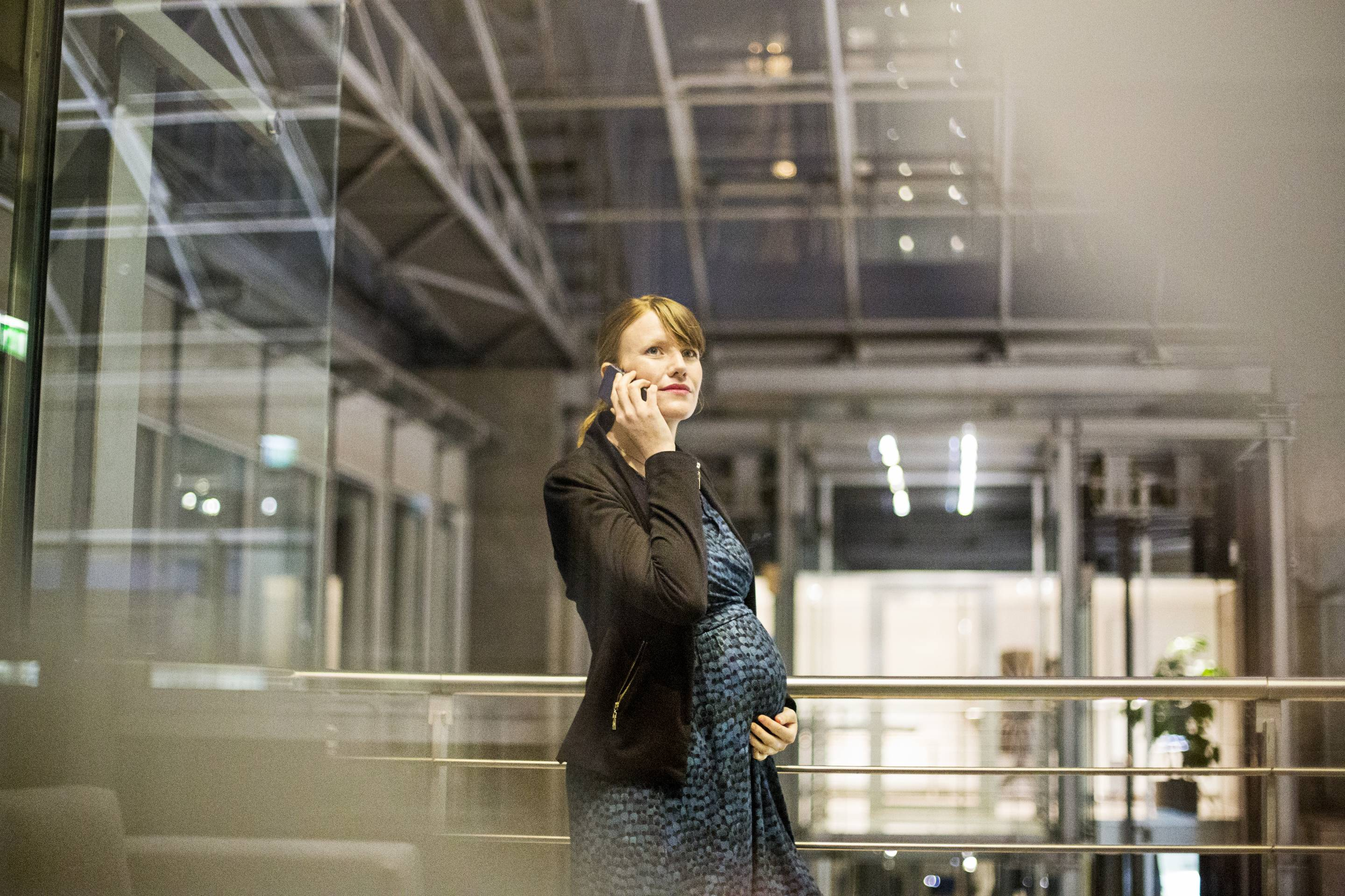 Beautiful pregnant business woman talking on the mobile phone