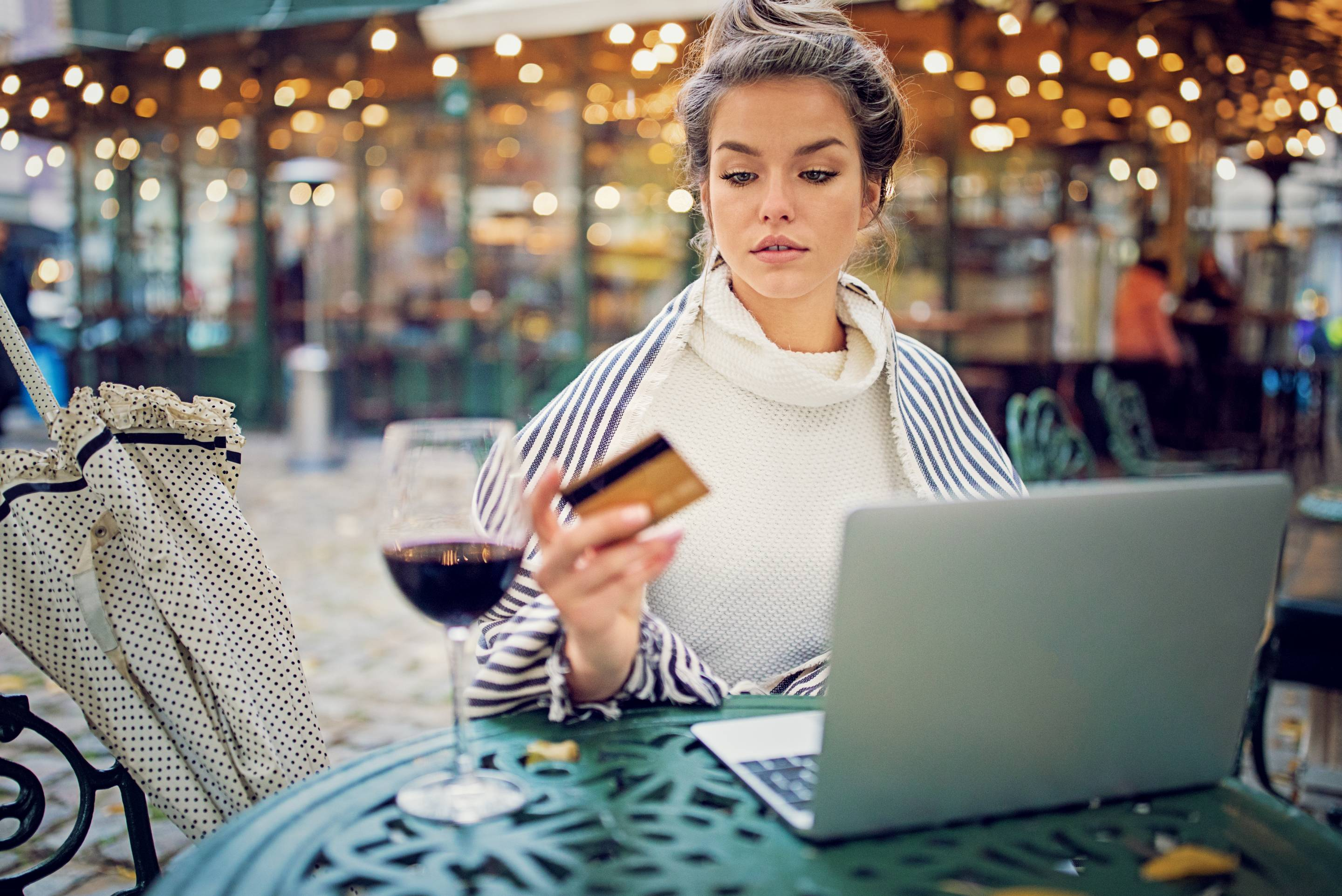 Young woman is shopping online using her credit card and laptop in a rainy day